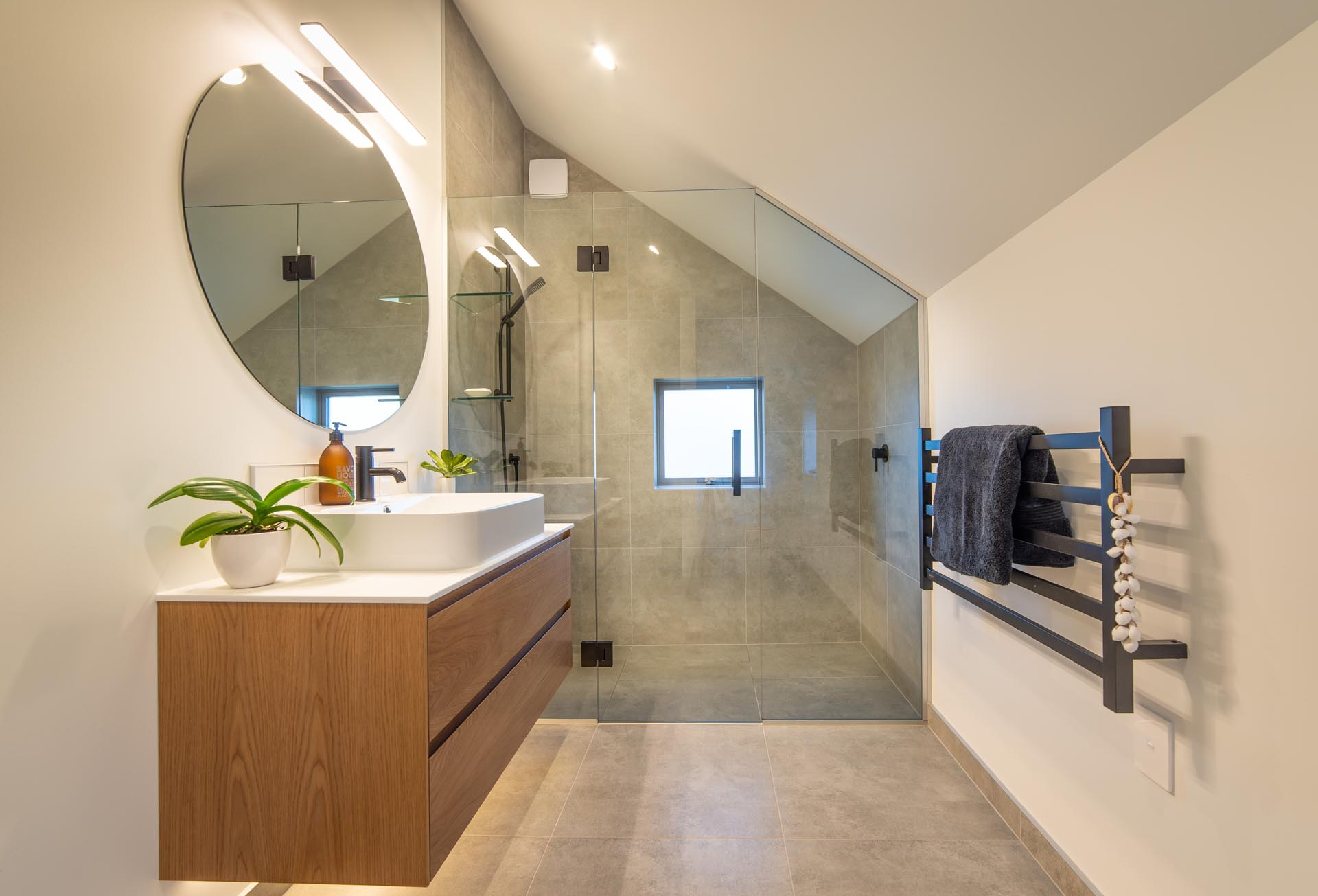 In this modern bathroom, the shower tile follows the line of the angled ceiling, while the wood vanity has hidden lighting underneath.