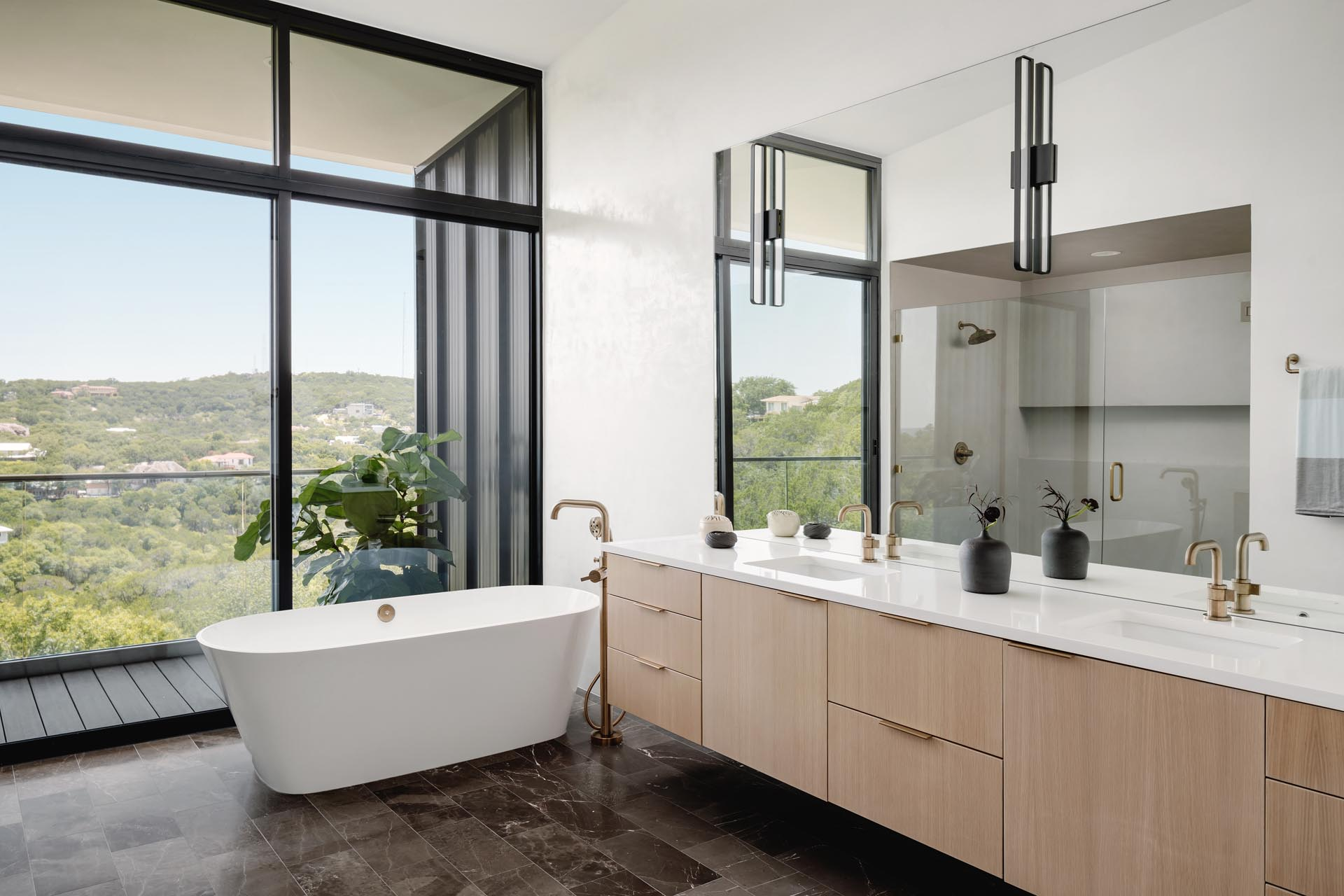 A modern bathroom with a balcony, freestanding bathtub, glass enclosed shower, and floating wood vanity.