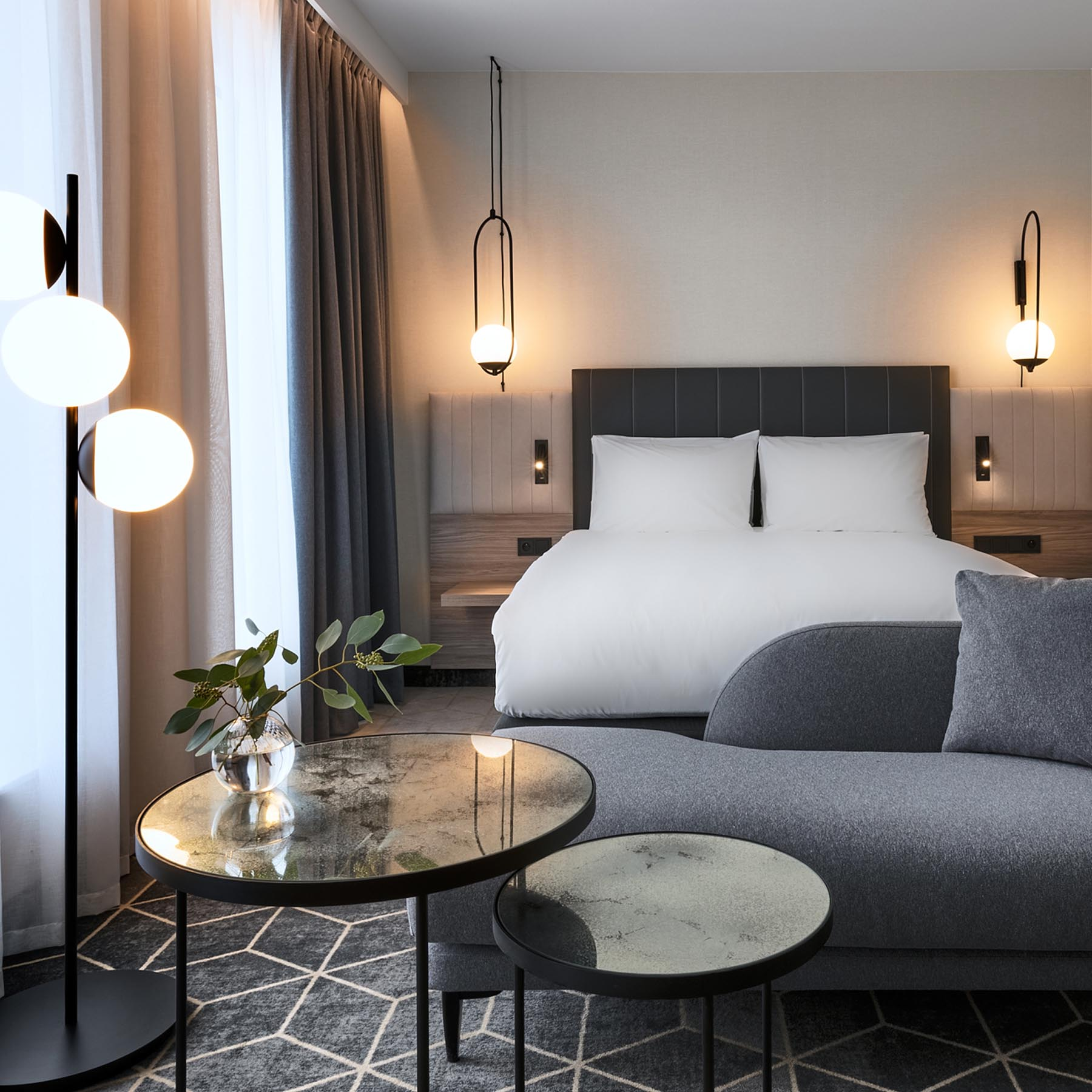 A hotel room with a gray, white, and wood interior.