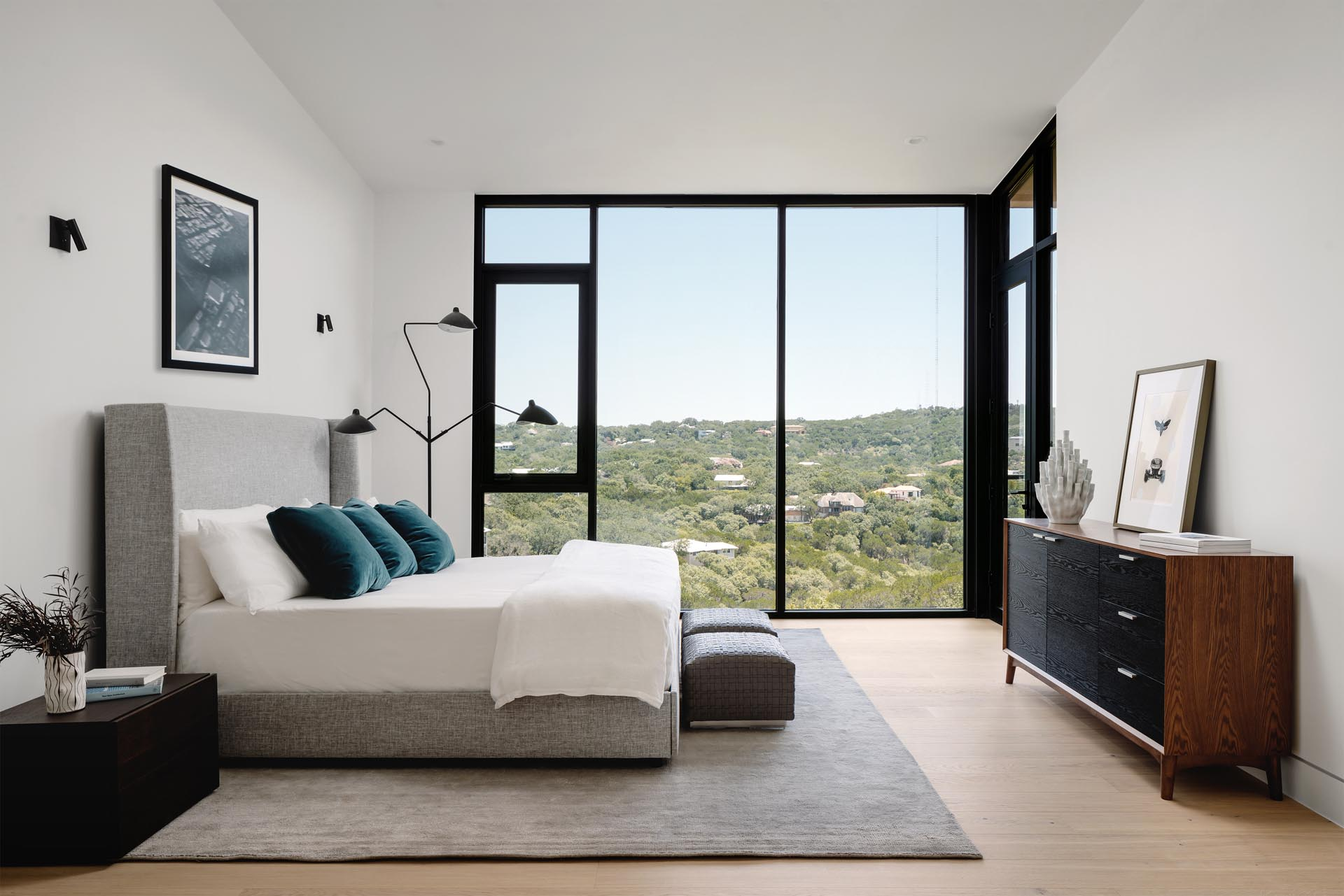A modern bedroom with floor-to-ceiling windows that allow the tree view to be enjoyed from the bed.