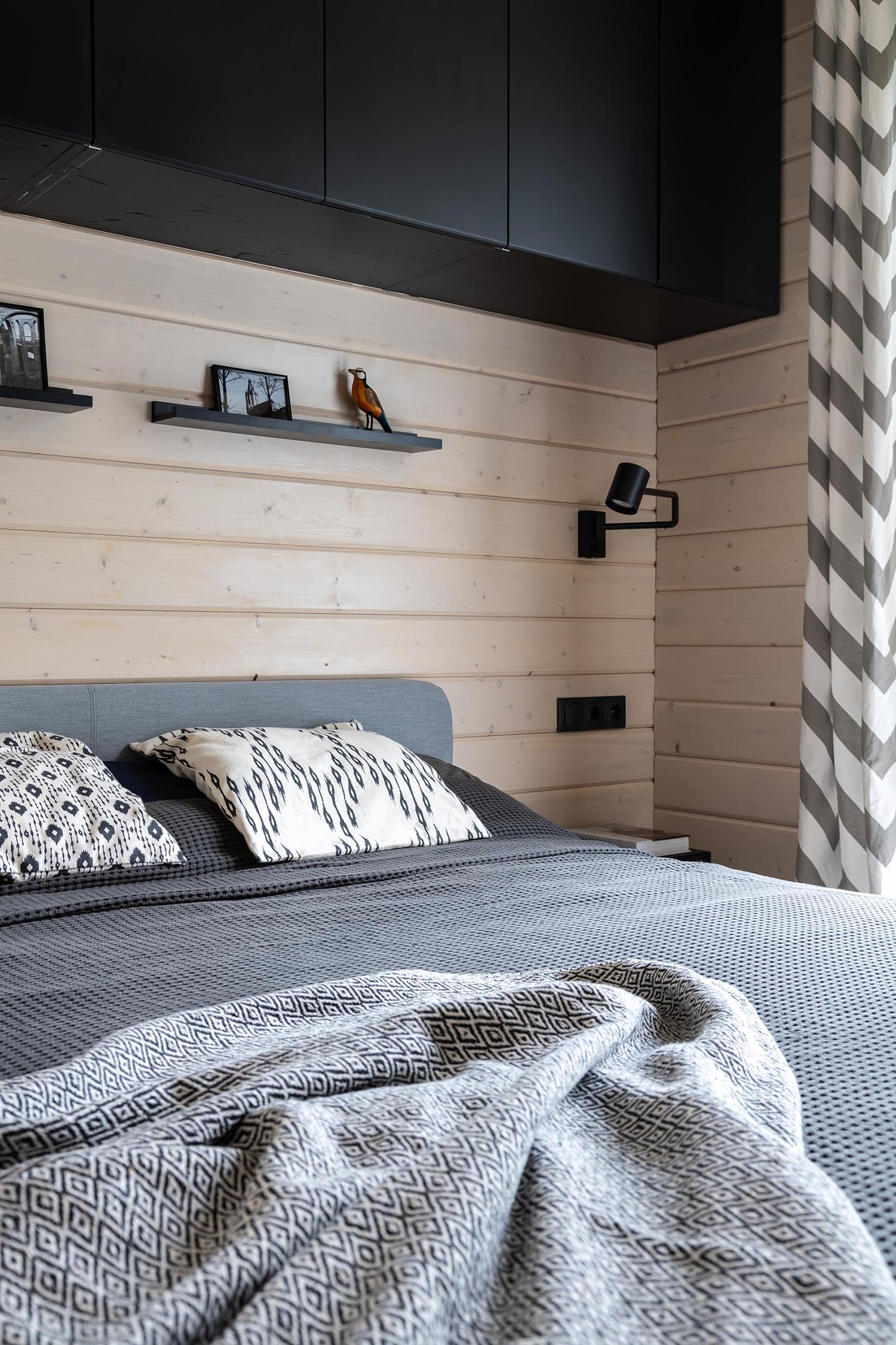 A modern barn-inspired bedroom with tongue and groove wood siding and black accents.