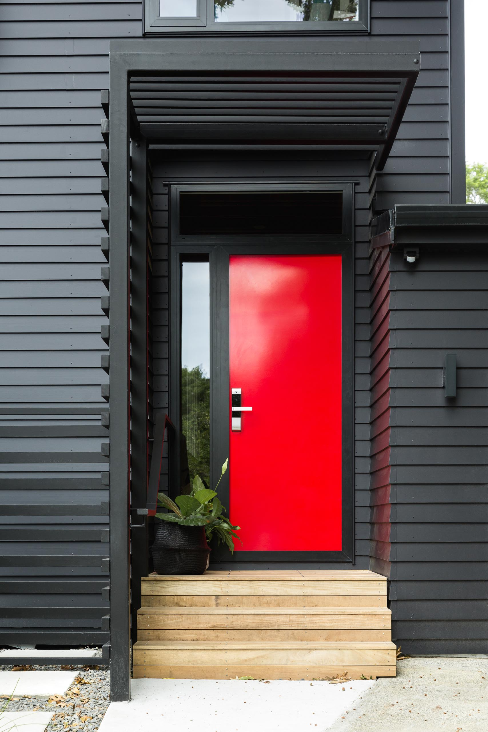 This modern house is in cedar weatherboards, and painted black creating a bold exterior, while the bright red door adds a strong contrasting design element.