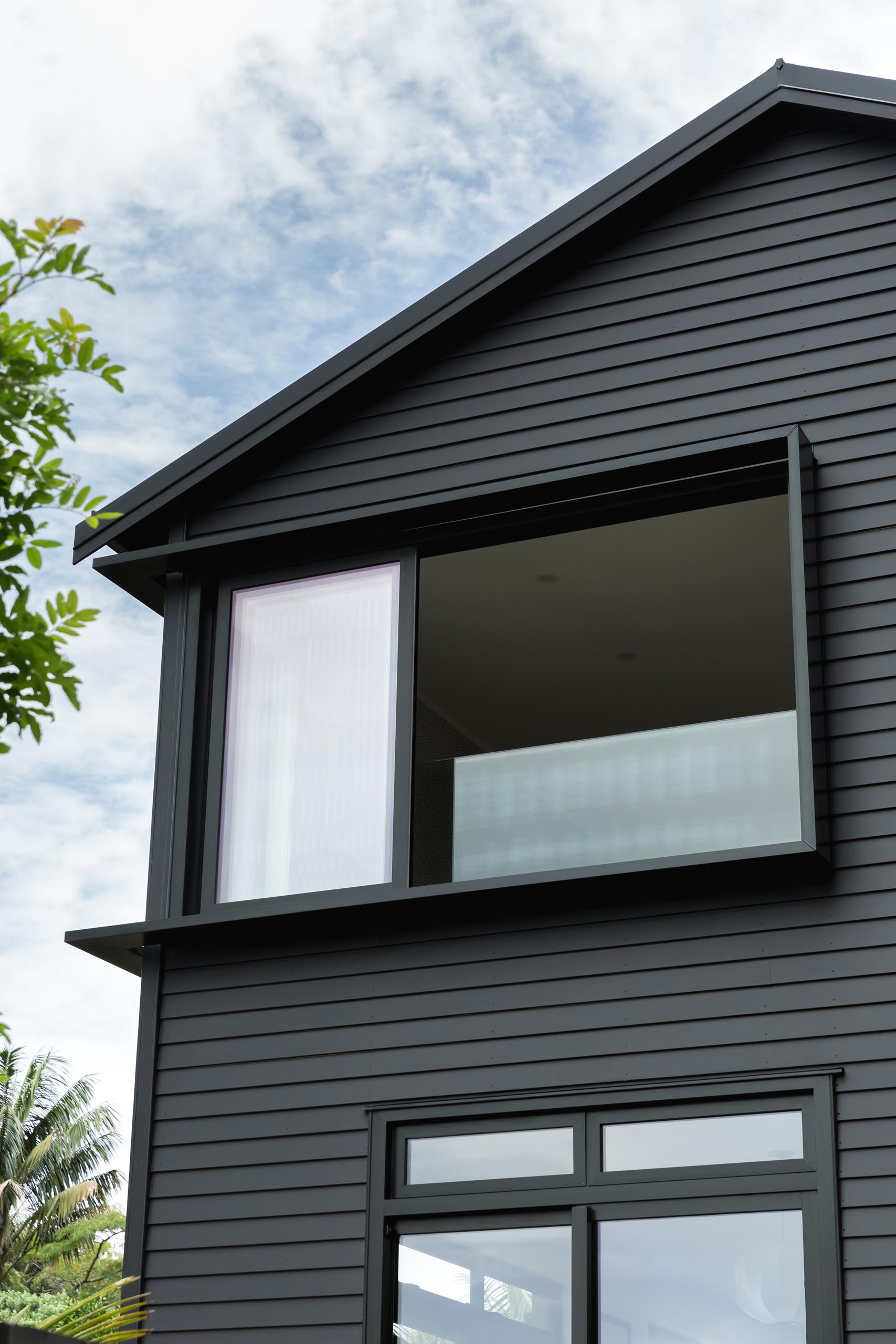 The window surround details of this modern black house are a common feature in the area, and were used to create additional light and shade detailing to the facade.