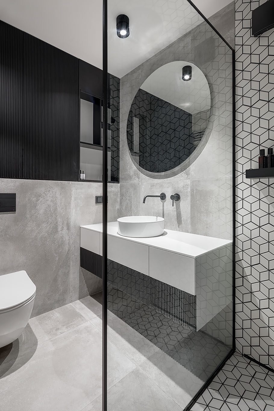 The bathroom includes a white, gray and black interior, with a bright white vanity, concrete wall and floor tiles, white geometric tiles with black grout, and a custom black shelving niche.