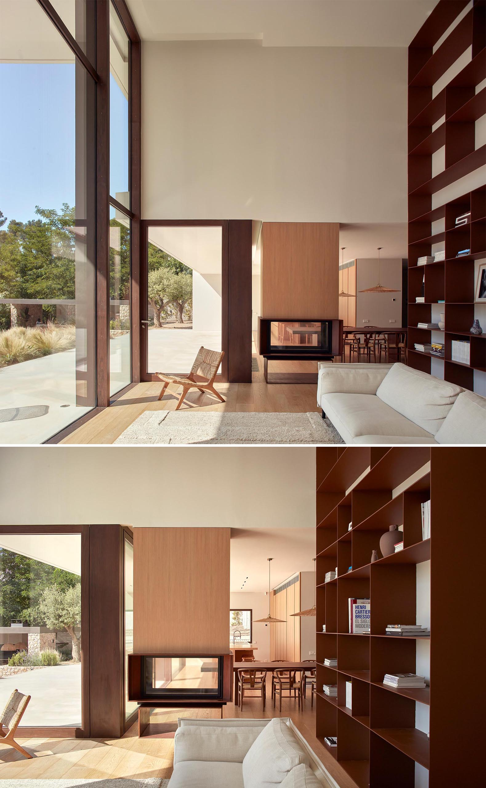 A modern living room with a double-height bookshelf and a see-through fireplace.