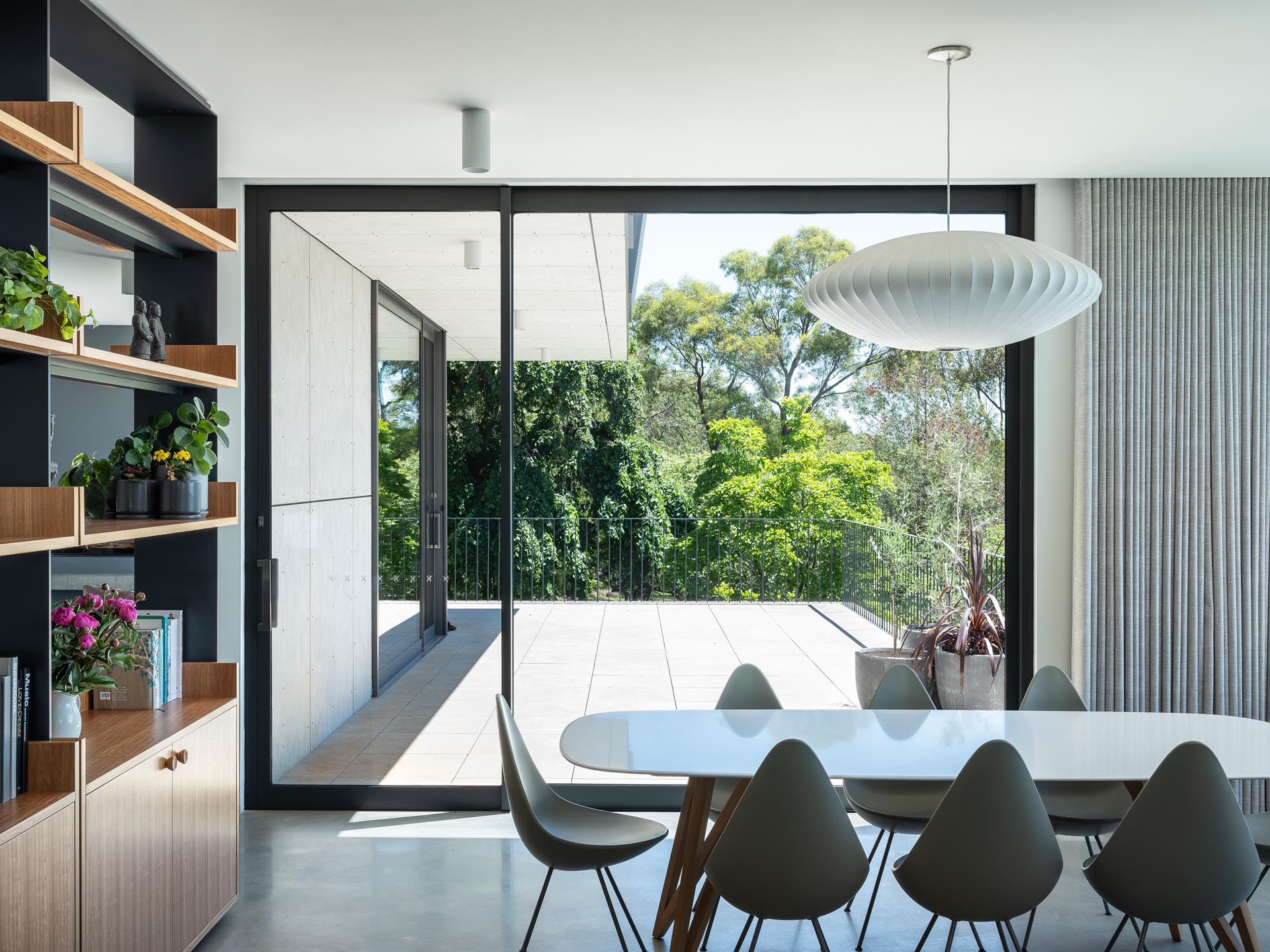 A modern dining room with a custom shelving unit, has access to a deck.