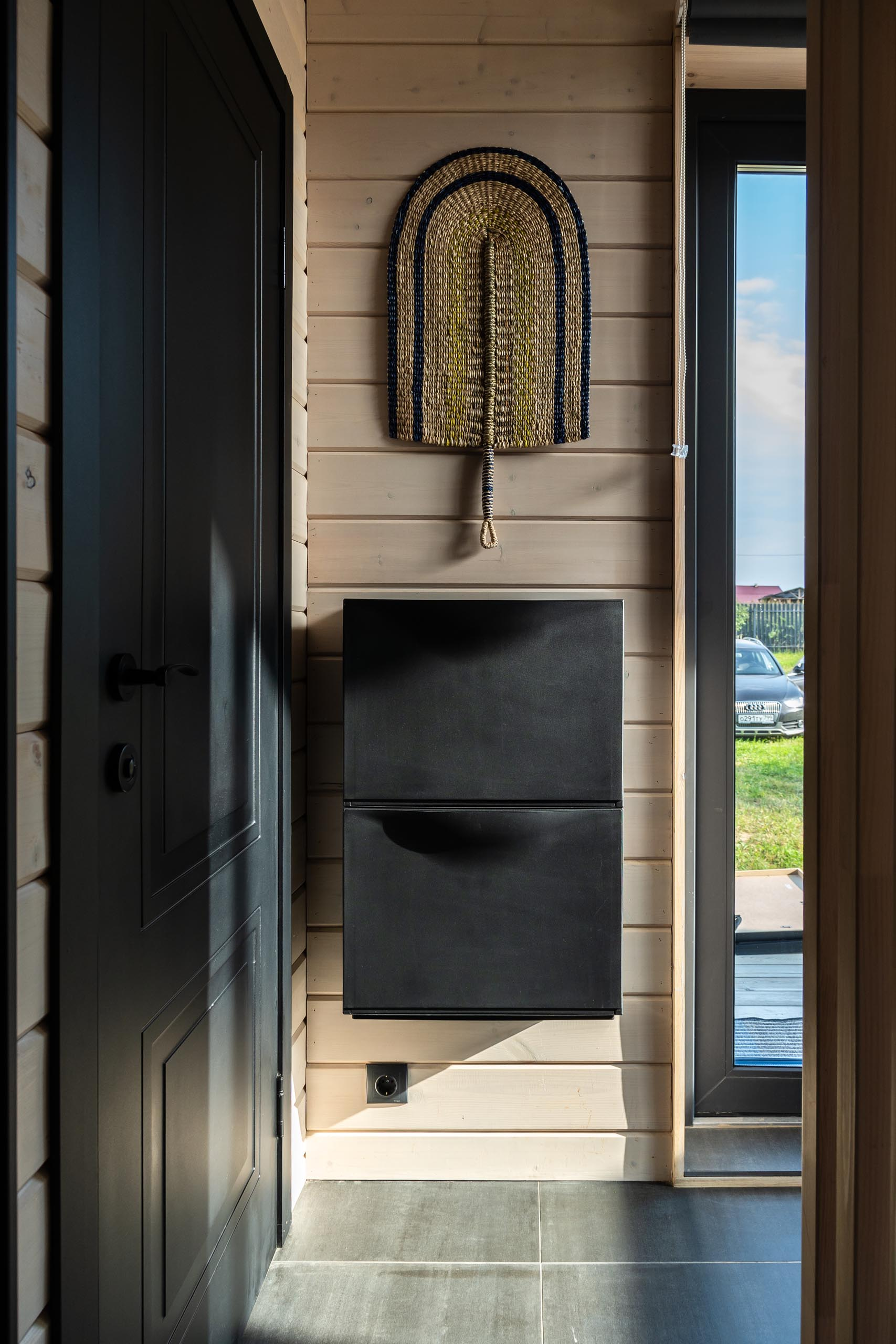 A modern barn-inspired entryway with tongue and groove wood siding and black accents.