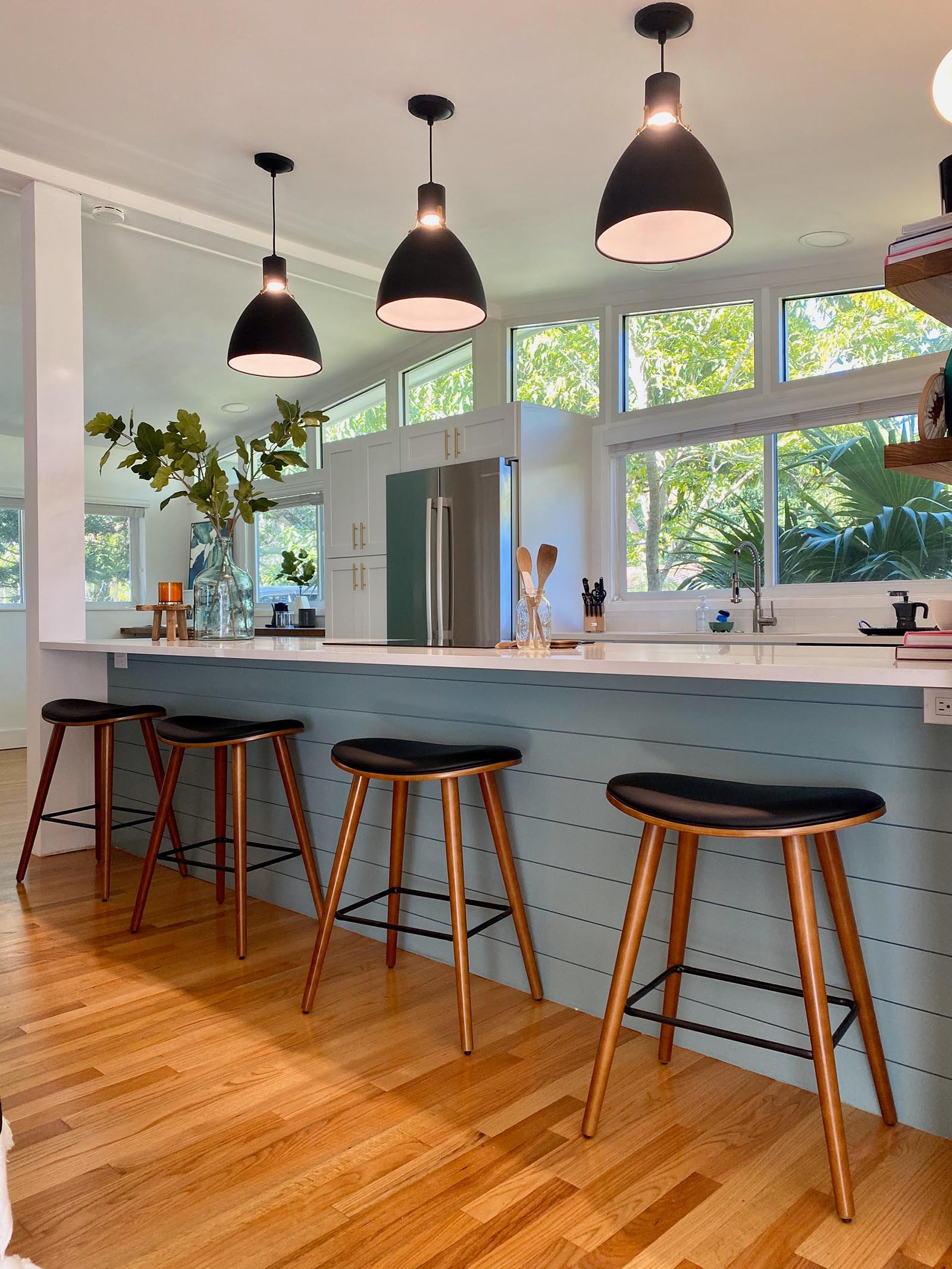 A modern and open kitchen with a peninsula, white cabinets, open wood shelving, and hexagonal floor tiles.