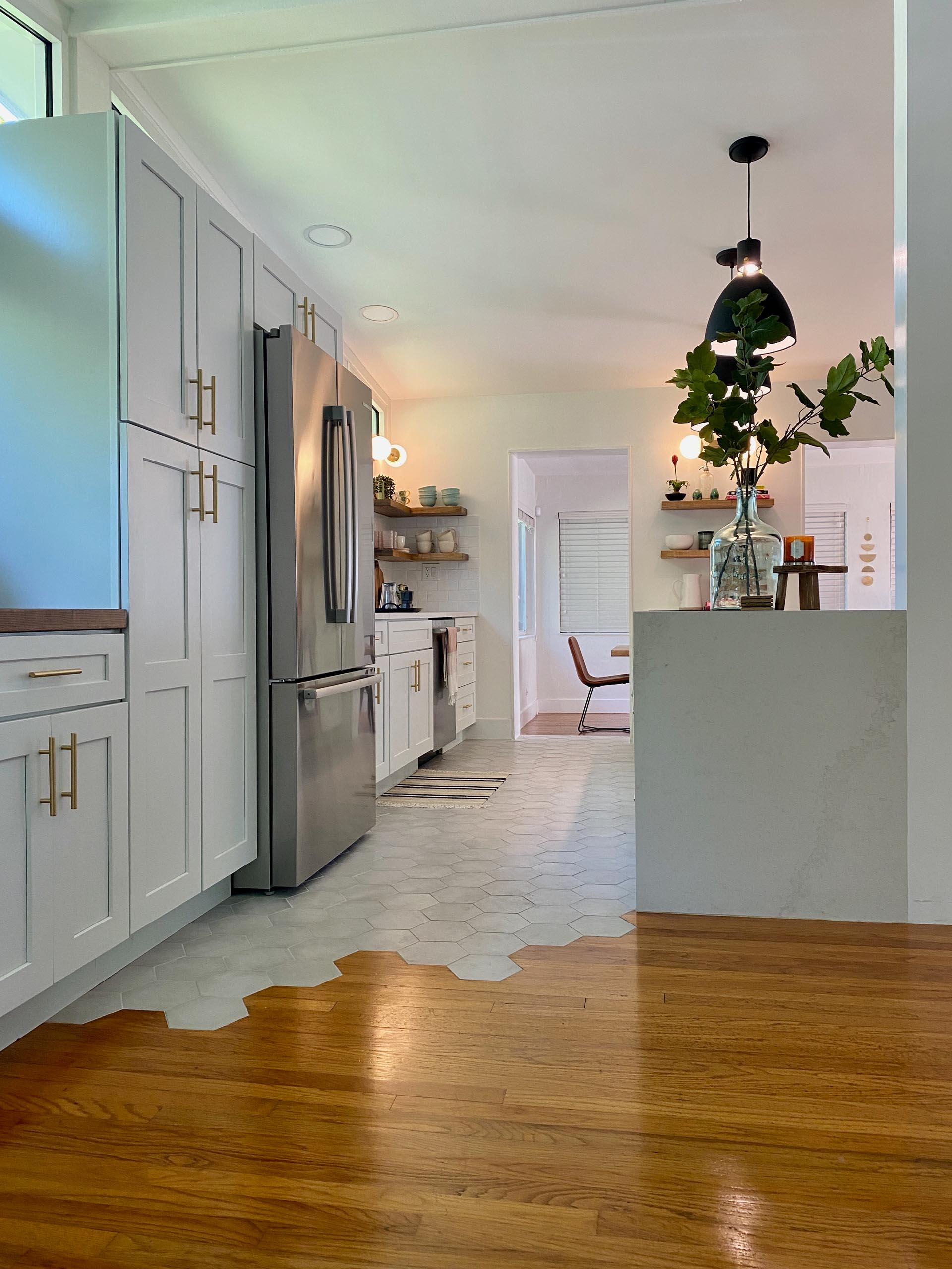 A modern and open kitchen with a peninsula, white cabinets, gold accents, open wood shelving, and hexagonal floor tiles.