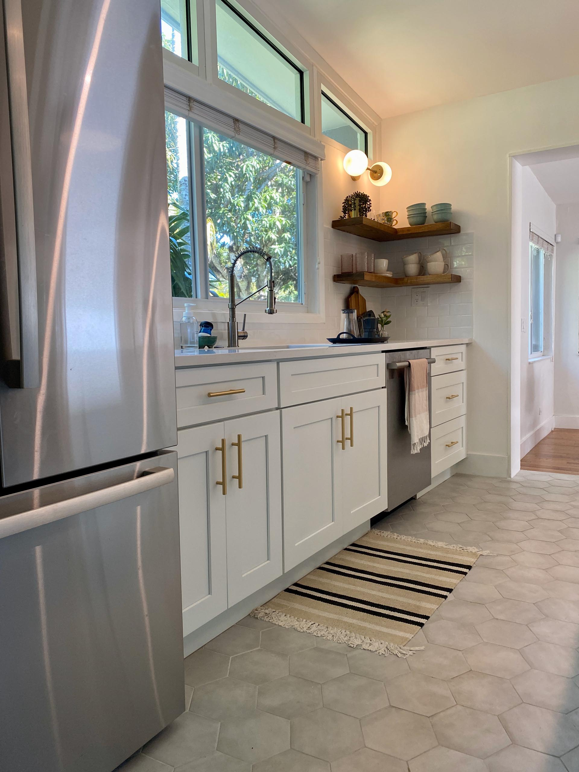 A modern and open kitchen with a peninsula, white cabinets, gold accents, floating wood shelving, and hexagonal floor tiles.