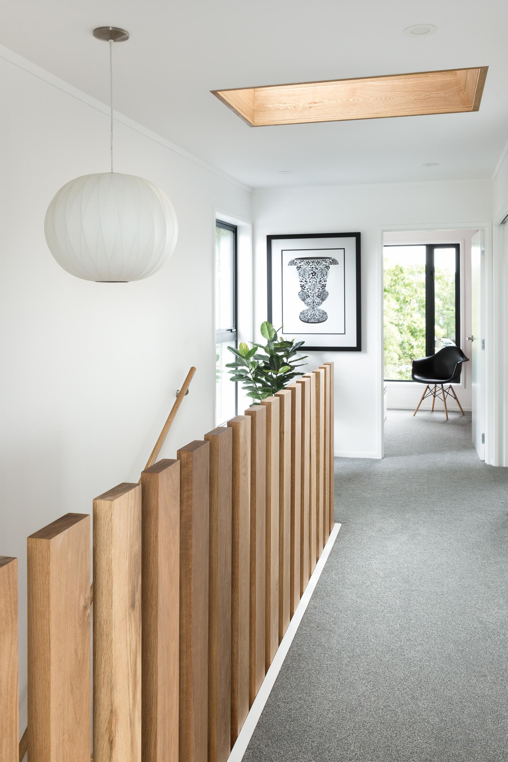 This modern home includes stair balusters are engineered to float above the landing without being tied together. Beyond is a glimpse of the oak tree that the design was inspired by, while the ceiling also features a wood lined skylight adding extra natural light to the stairwell below.
