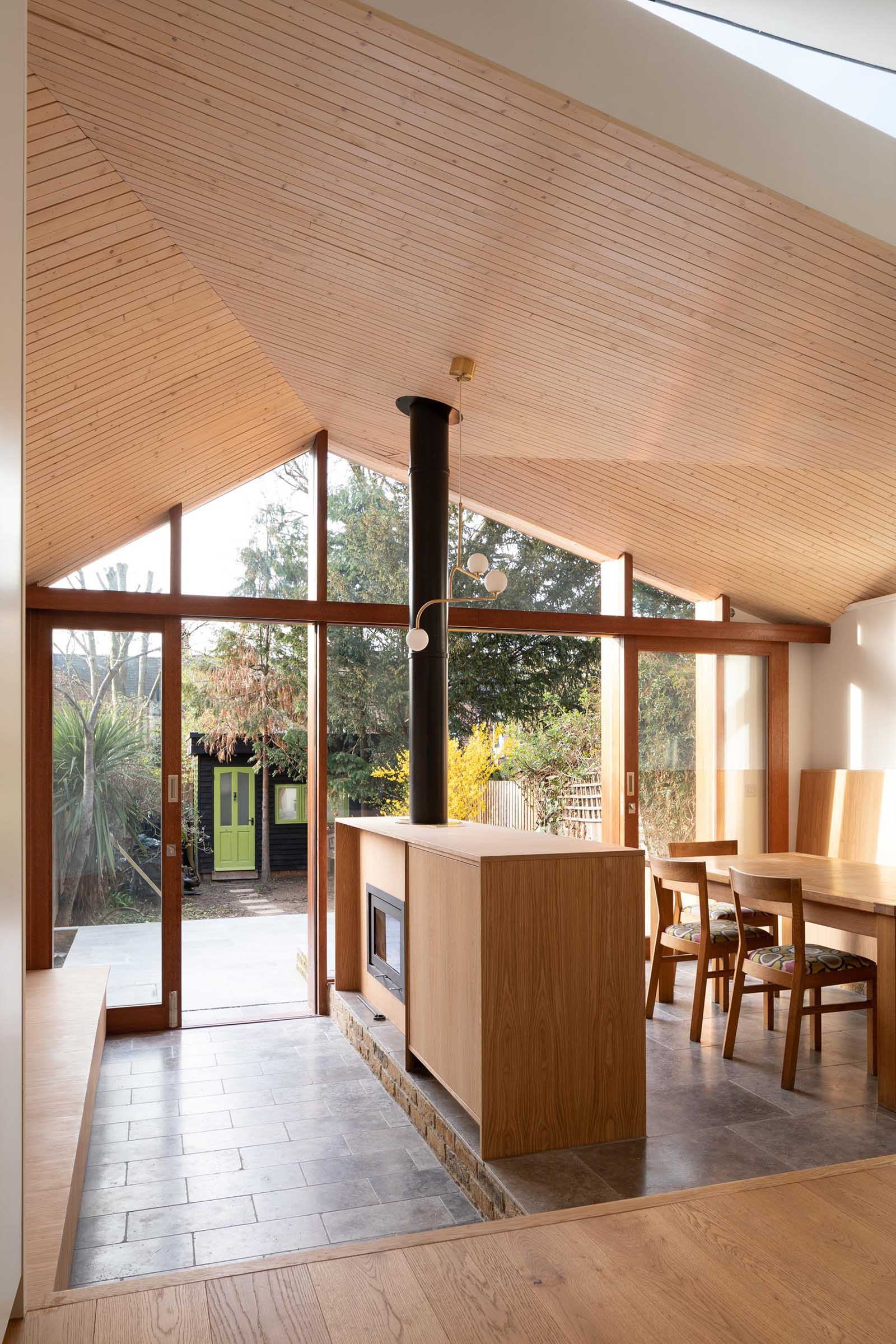 The interior of this new home addition includes an angled ceiling lined with light wood, which creates glimpses of the sky in different directions.