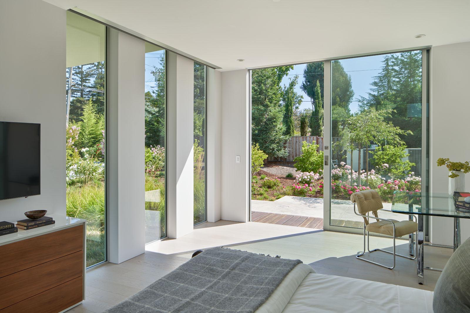 The bedroom has floor-to-ceiling windows and a sliding glass door that opens to a patio and the garden.