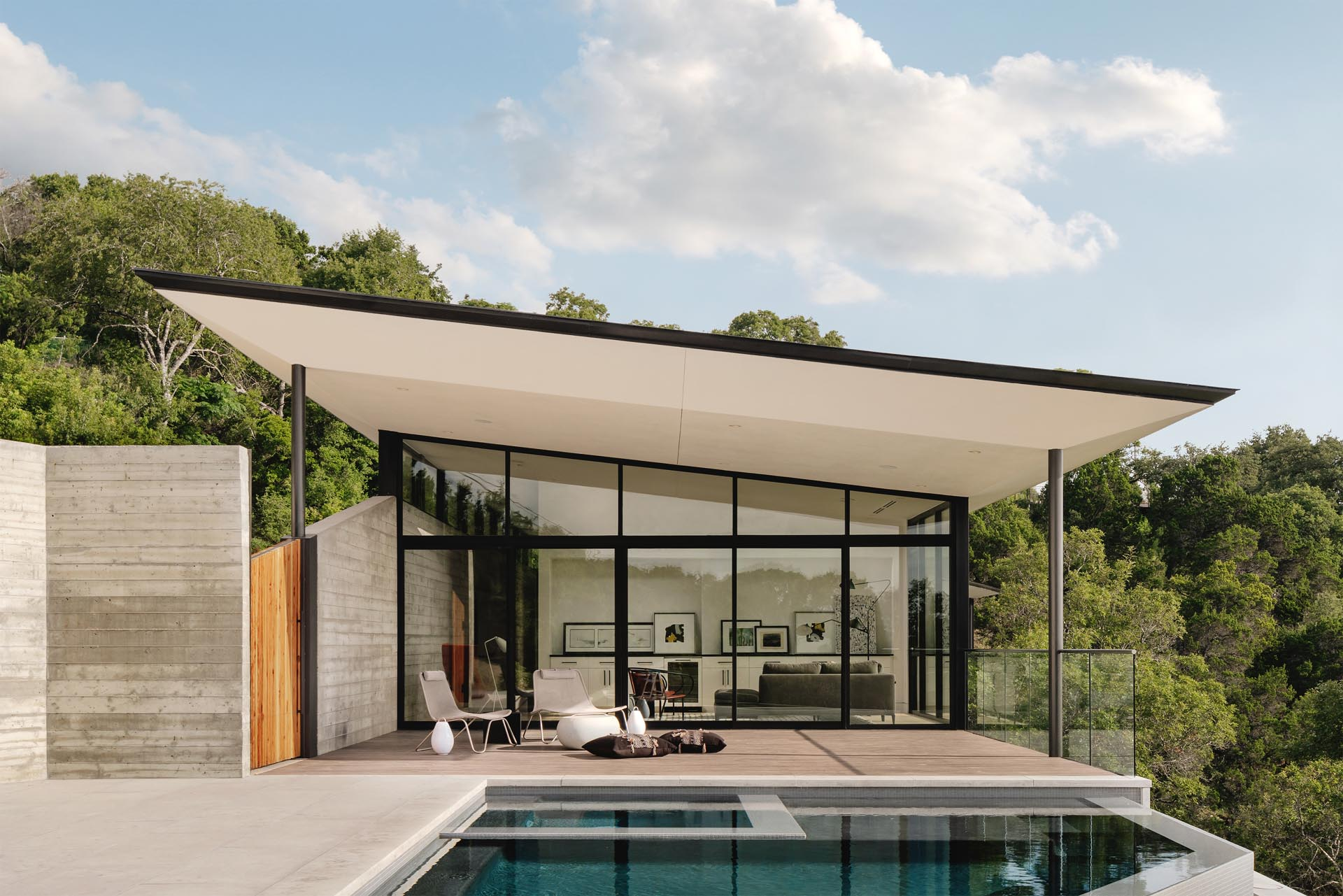 The boomerang shape of the home accentuate the natural curvature of the land, while high walls lined with clerestory windows create a buffer between the busy adjacent road while also balancing light throughout the day.
