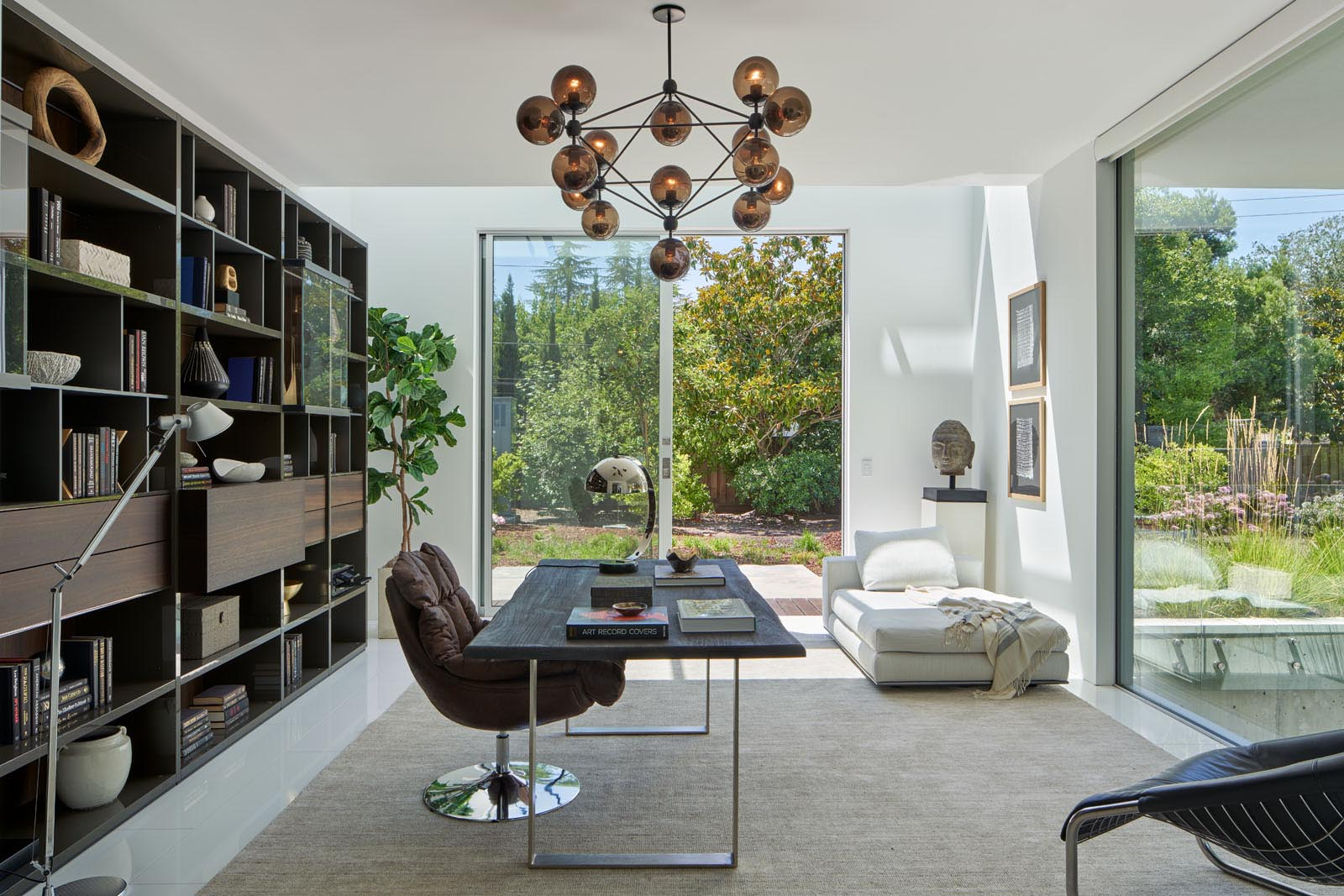 In a home office, a dark bookshelf provides a backdrop for the desk, while a sculptural light fixture adds interest to the room.