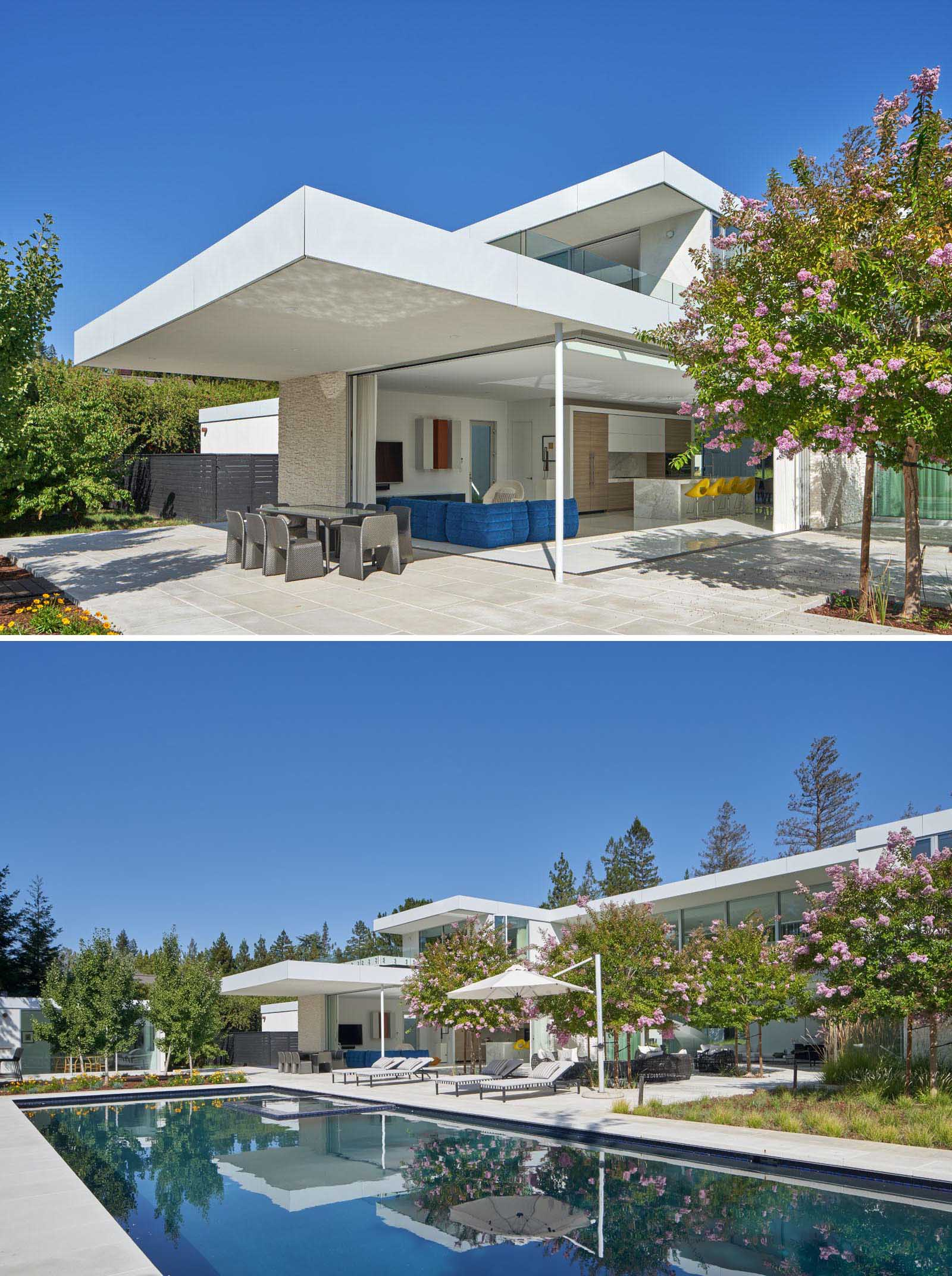 The outdoor spaces of this modern house include a covered dining patio, an lounge area, and a swimming pool.