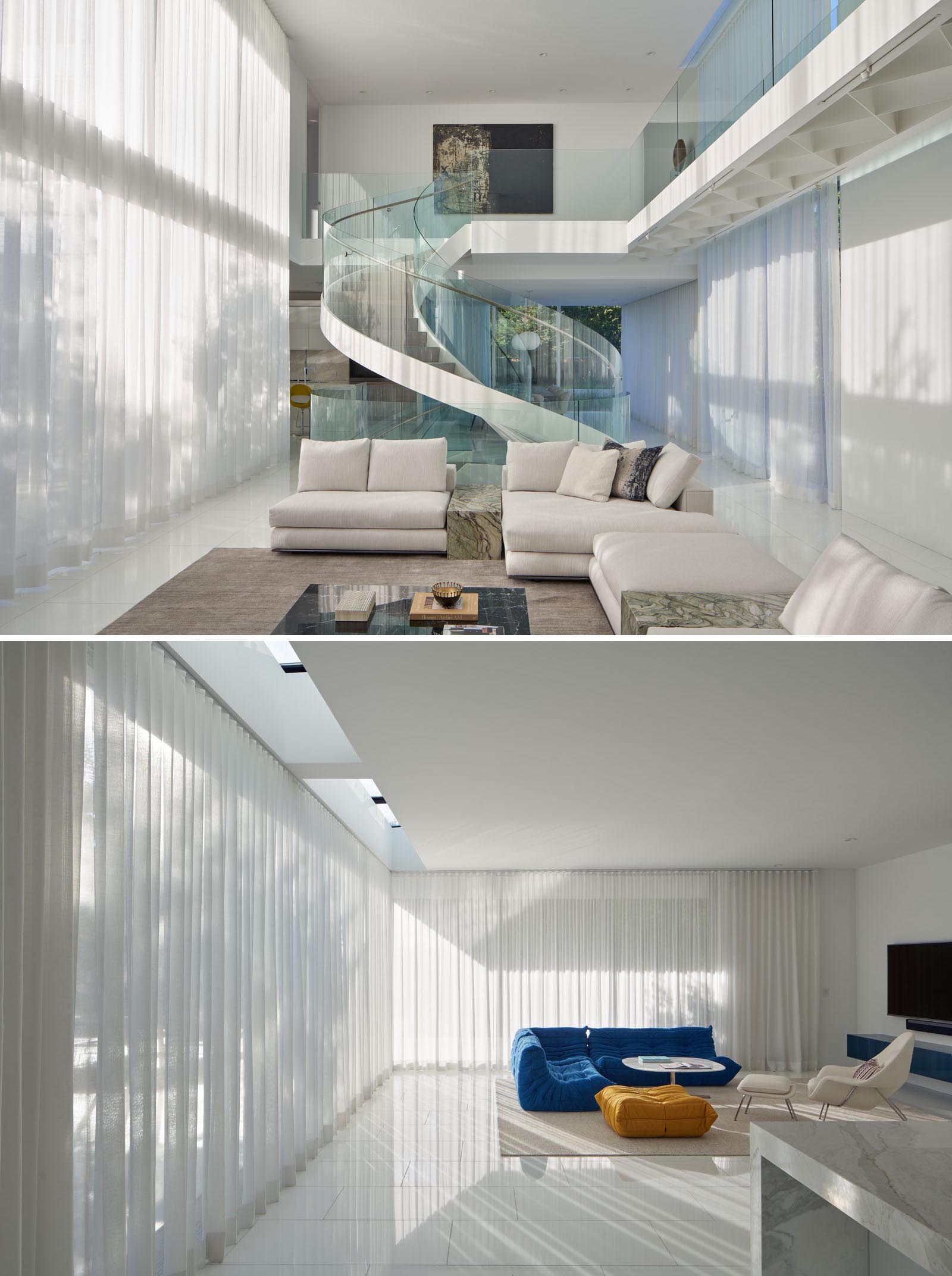 This modern living room has pocketing sliding glass doors that dissolve the boundary between inside and outside. At night, white curtains can be closed for privacy.