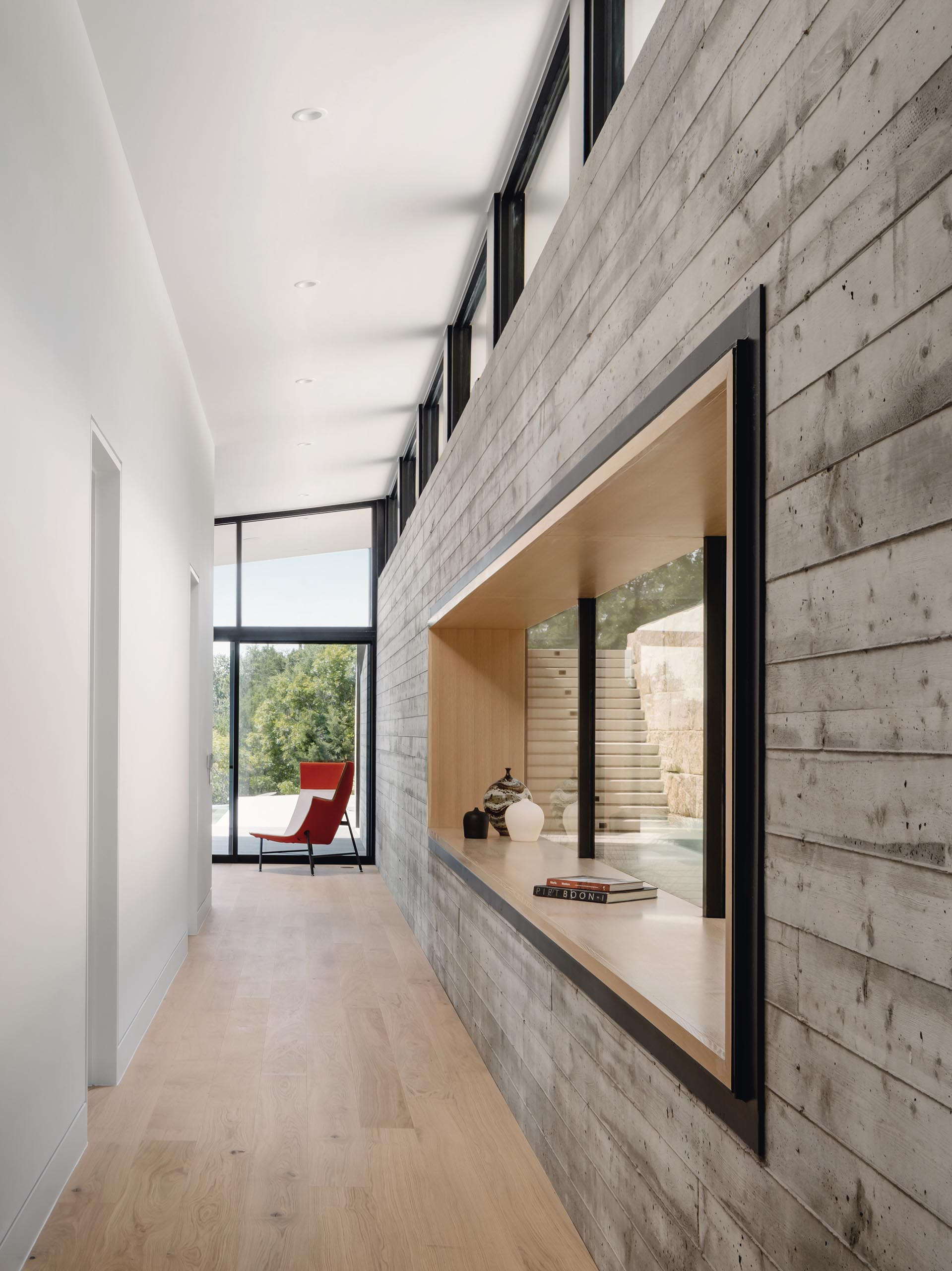 A hallway connecting the two living rooms provides a close-up look at the board-formed concrete wall, and access to the bedrooms and bathrooms.