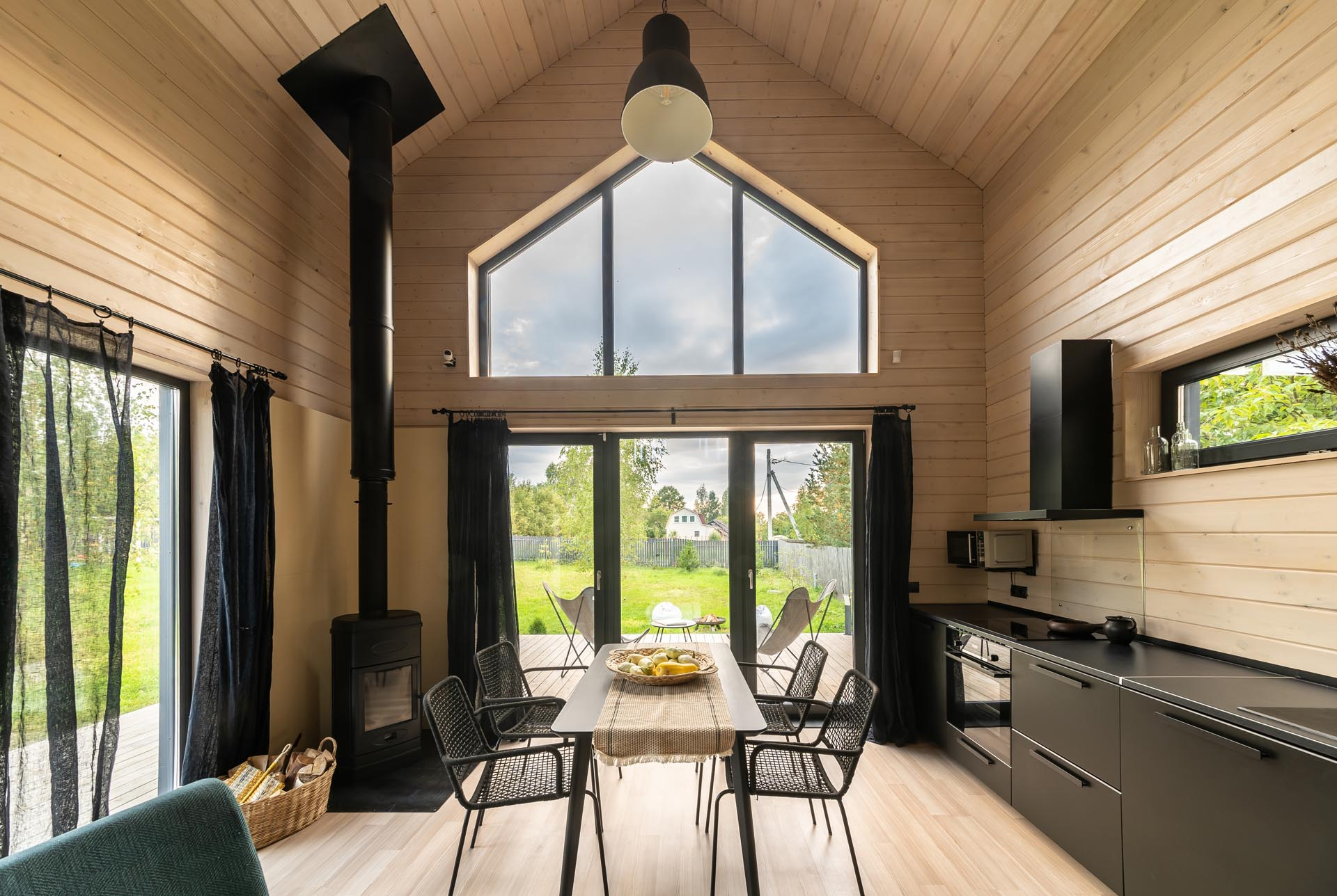 A modern barn-inspired open plan dining area and kitchen with tongue and groove wood siding and black accents, like the kitchen cabinets, the fireplace, the curtains, and furniture.