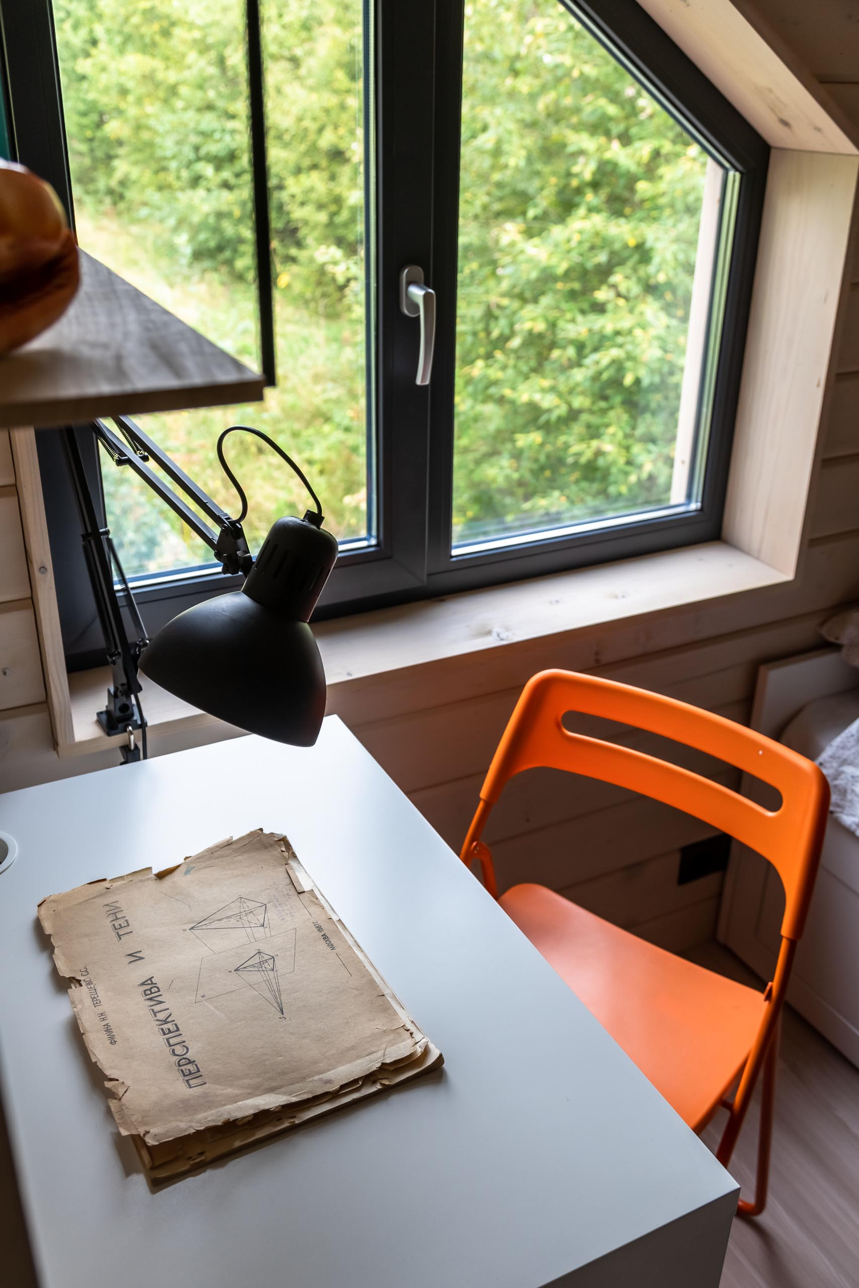 A modern kid's bedroom with tongue and groove wood siding, a white desk, black light, and orange chair.