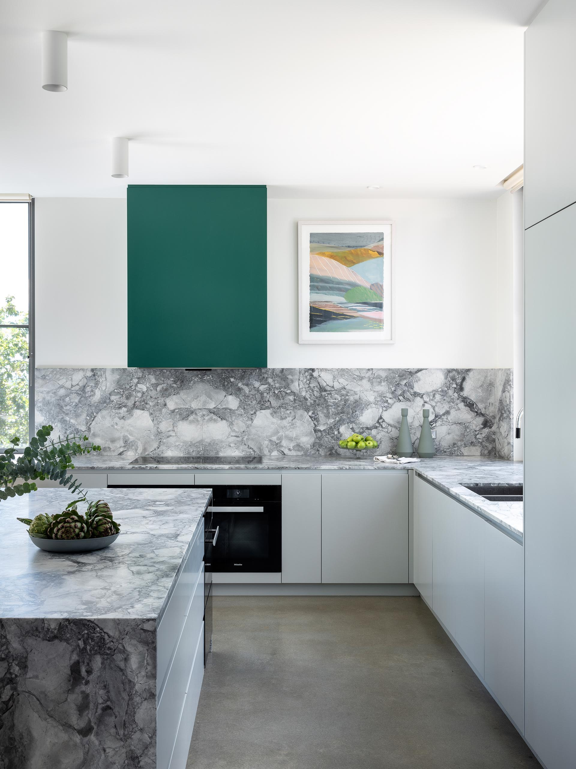 This kitchen has minimalist light gray cabinets that complement the marble countertops and concrete floors, while green accents add a pop of color.
