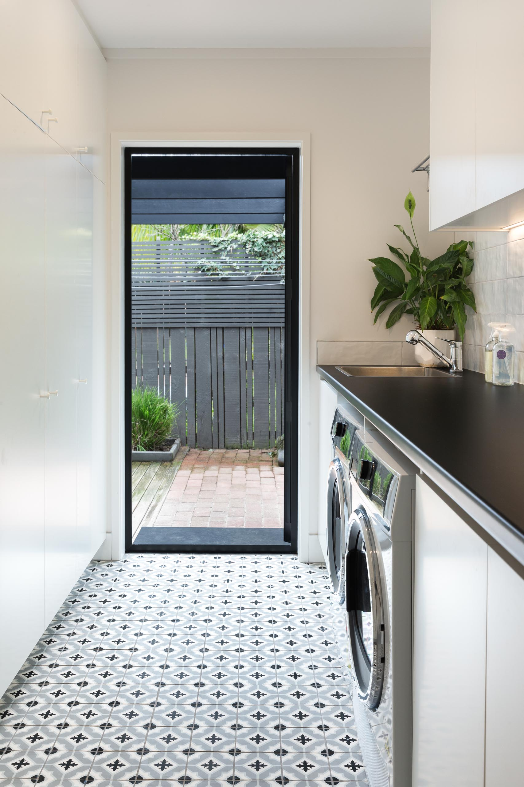 This modern laundry room has been designed with patterned floor tiles, floor-to-ceiling cabinets that add plenty of storage, and a black countertop travels across both the washing machine and dryer, and complements the black door frame.