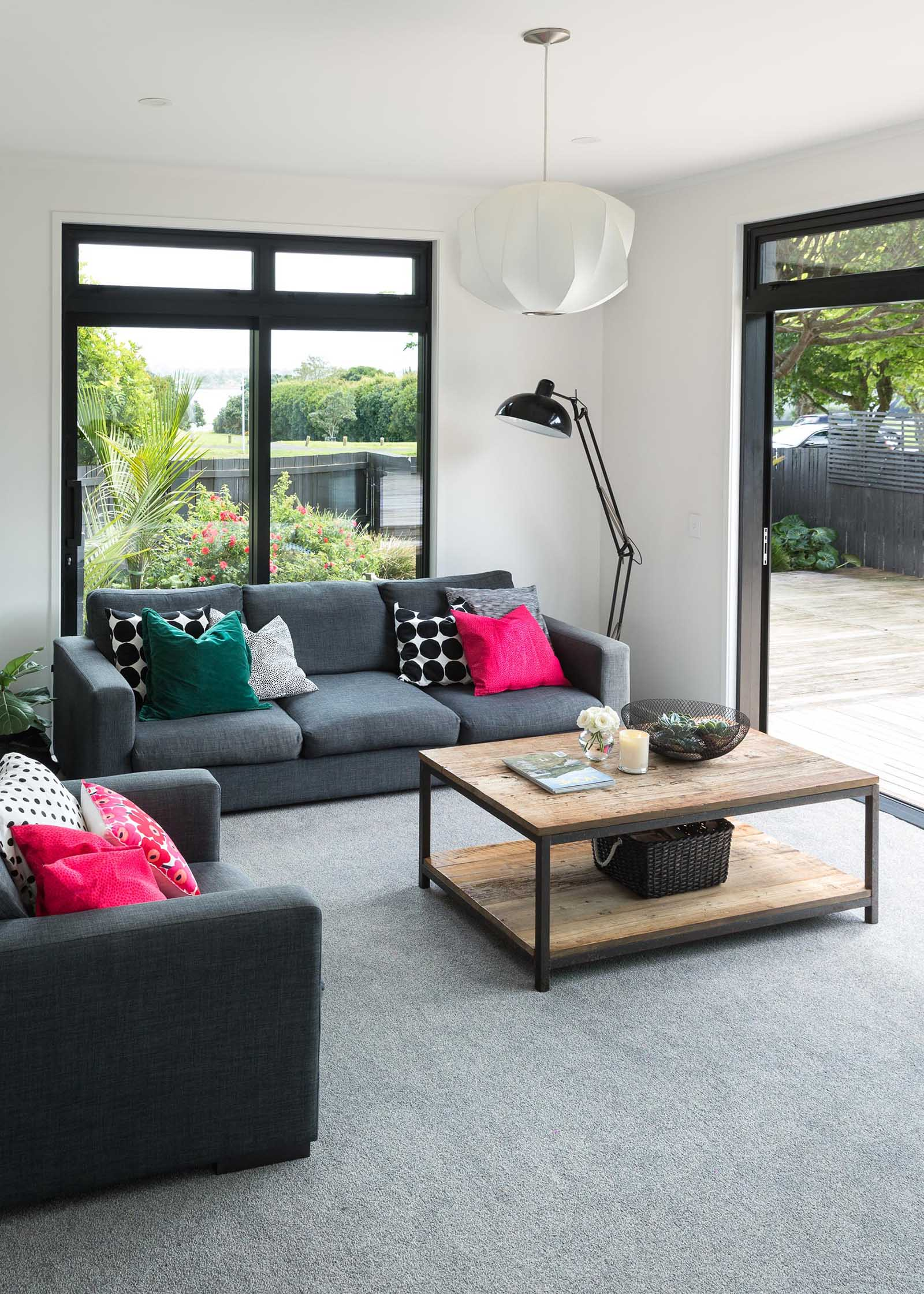 This modern living room includes white walls, grey carpet, and bold black window frames.