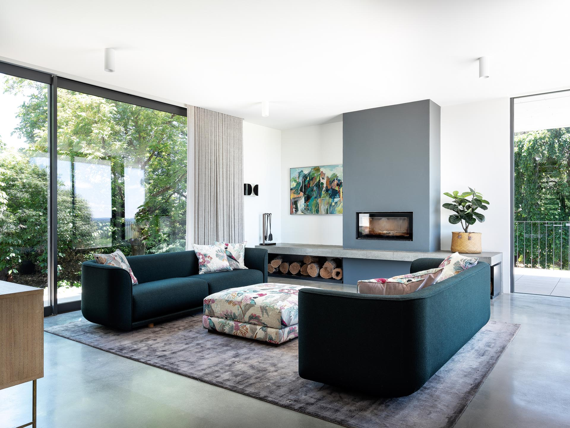 This modern living room palette includes rich greens, textured marble, timber, and touches of florals and pinks in the upholstery, soft furnishings, and art.