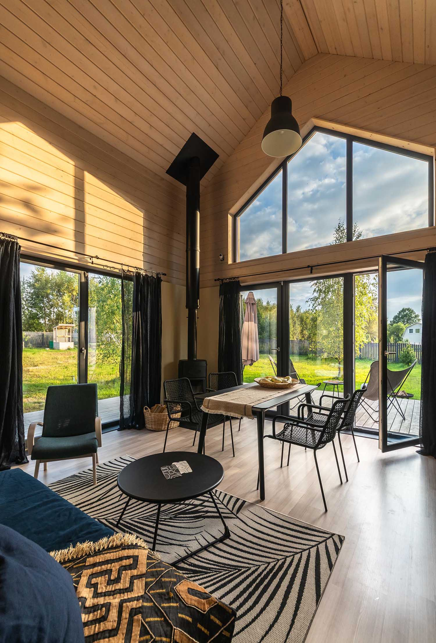 A modern barn-inspired living room with tongue and groove wood siding and black accents, like a fireplace, the curtains, and furniture.