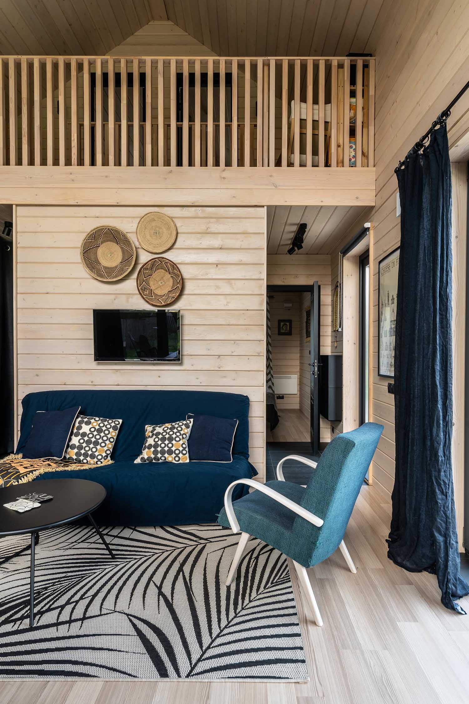 A modern barn-inspired living room with tongue and groove wood siding and black accents.