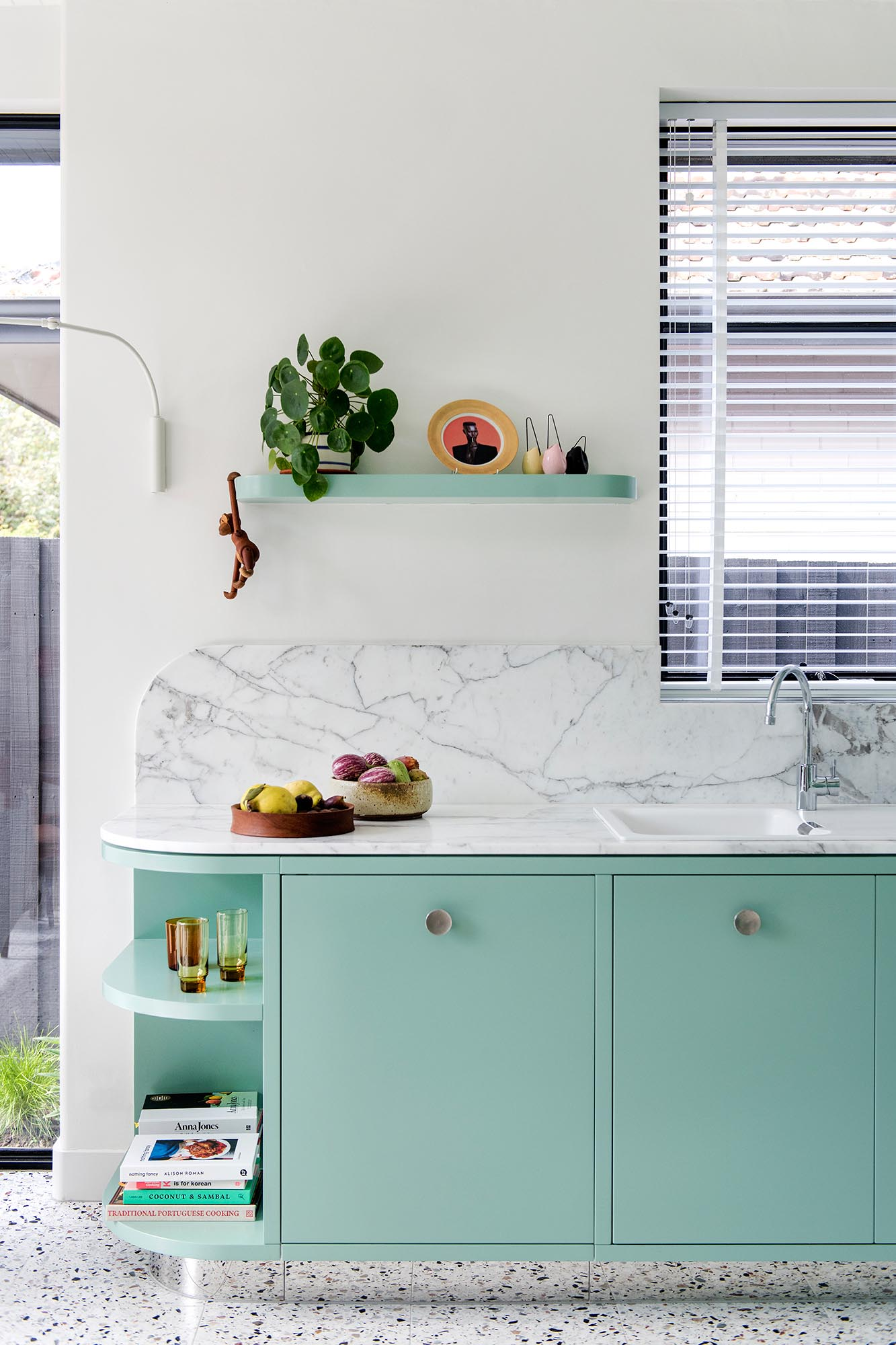 A modern mint green kitchen with Calacatta Statuario countertops, Terrazzo flooring, and white walls and ceiling.