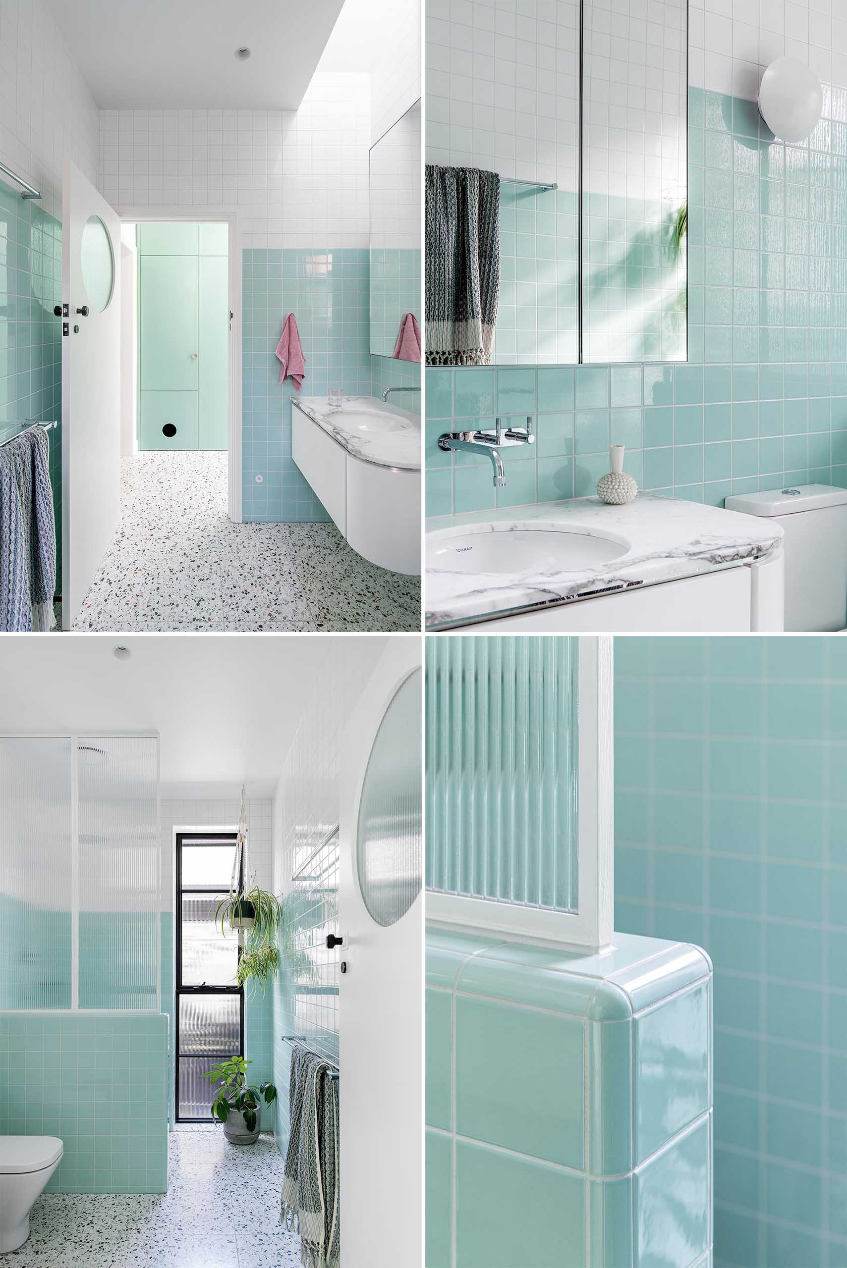 A modern bathroom with white and mint green tiles, a curved vanity, and walk-in shower.