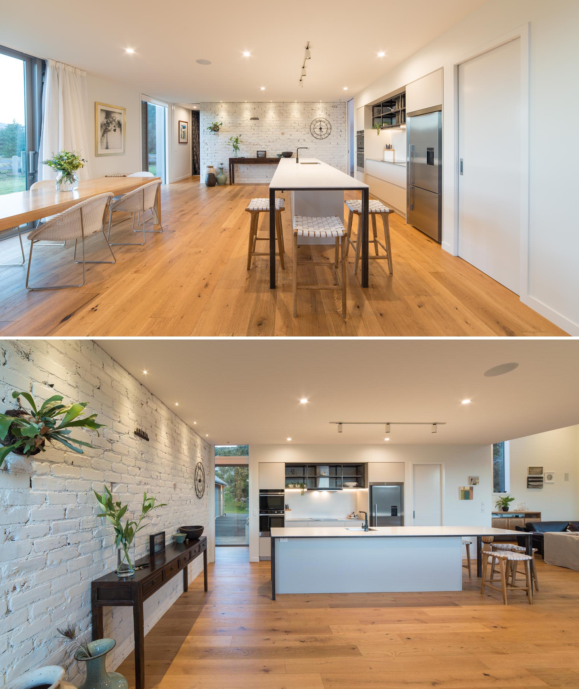 An open plan kitchen and dining area that had a white painted brick wall.