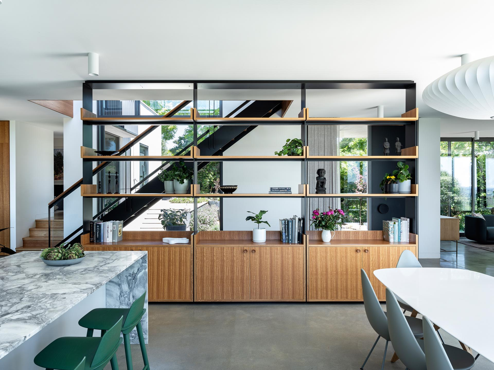One design element found in the interior of this modern home, is an open shelving unit that separates the entryway and hallway from the living, dining, and kitchen areas.
