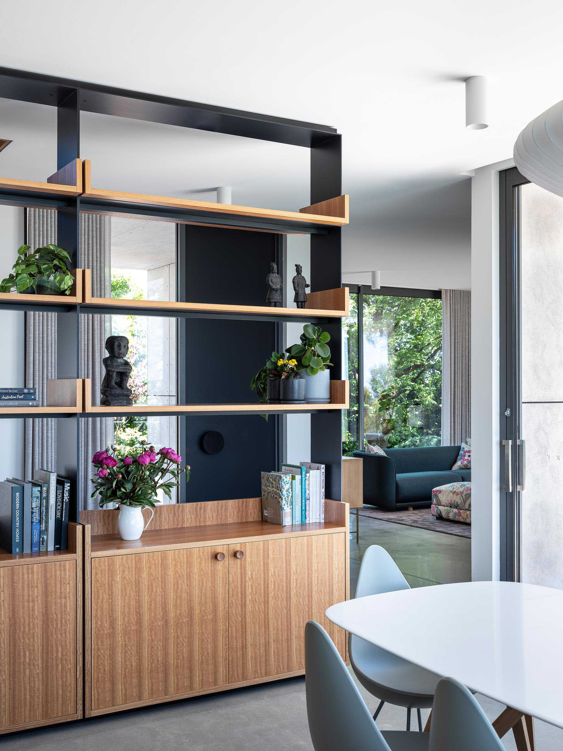 The blackbutt timber was also used to create lower cabinets, adding storage to the dining room. The shelving unit also allows the natural light from the windows to pass through, creating an open and bright interior.