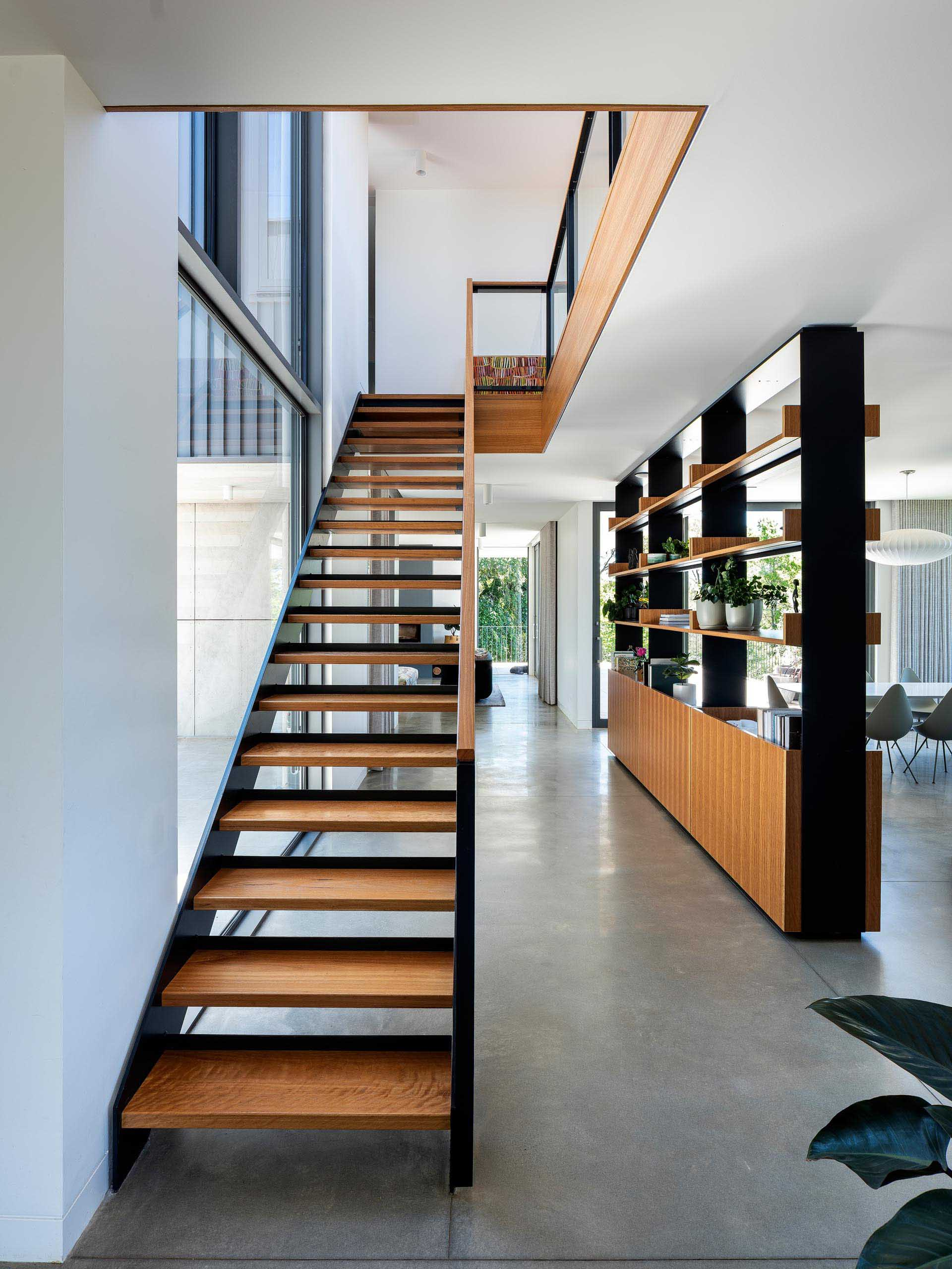 The shelving unit, with its black metal frame and wood accents, matches the design of the adjacent stairs, and contrasts other materials found throughout the home, like the heated concrete floors.