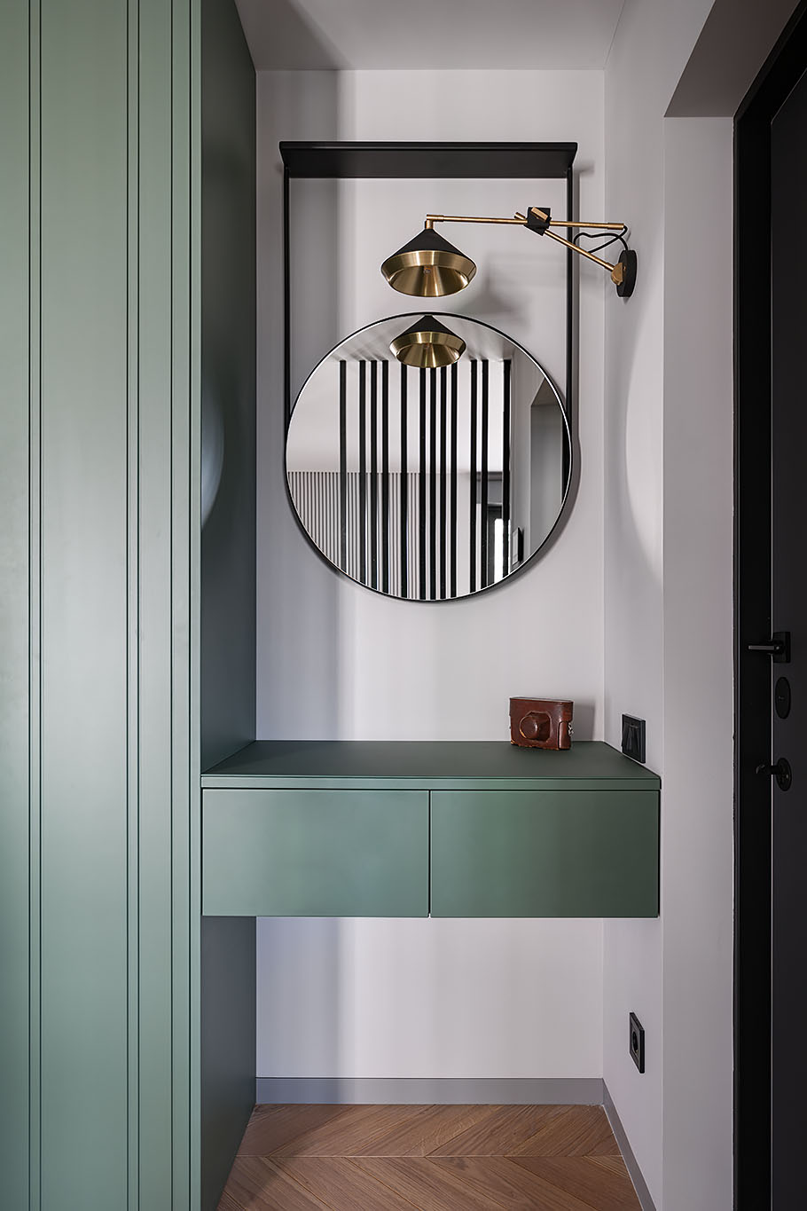 A small nook has been filled with a custom-built floating storage cabinet that also acts as an entryway table. Above, there's a round mirror, while a wall-mounted lamp adds light.