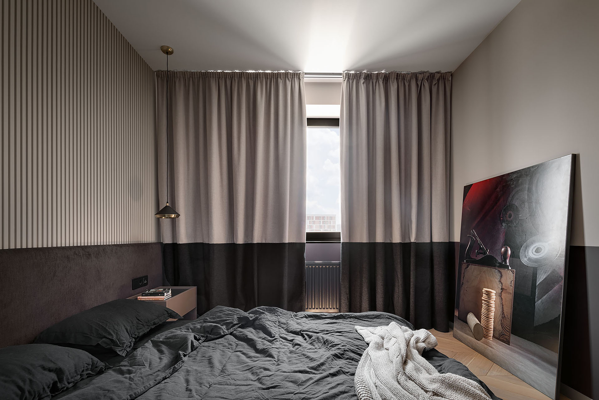 A two-tone bedroom includes different shades of chocolate and beige, a textured accent wall made from plaster, and two-tone curtains.