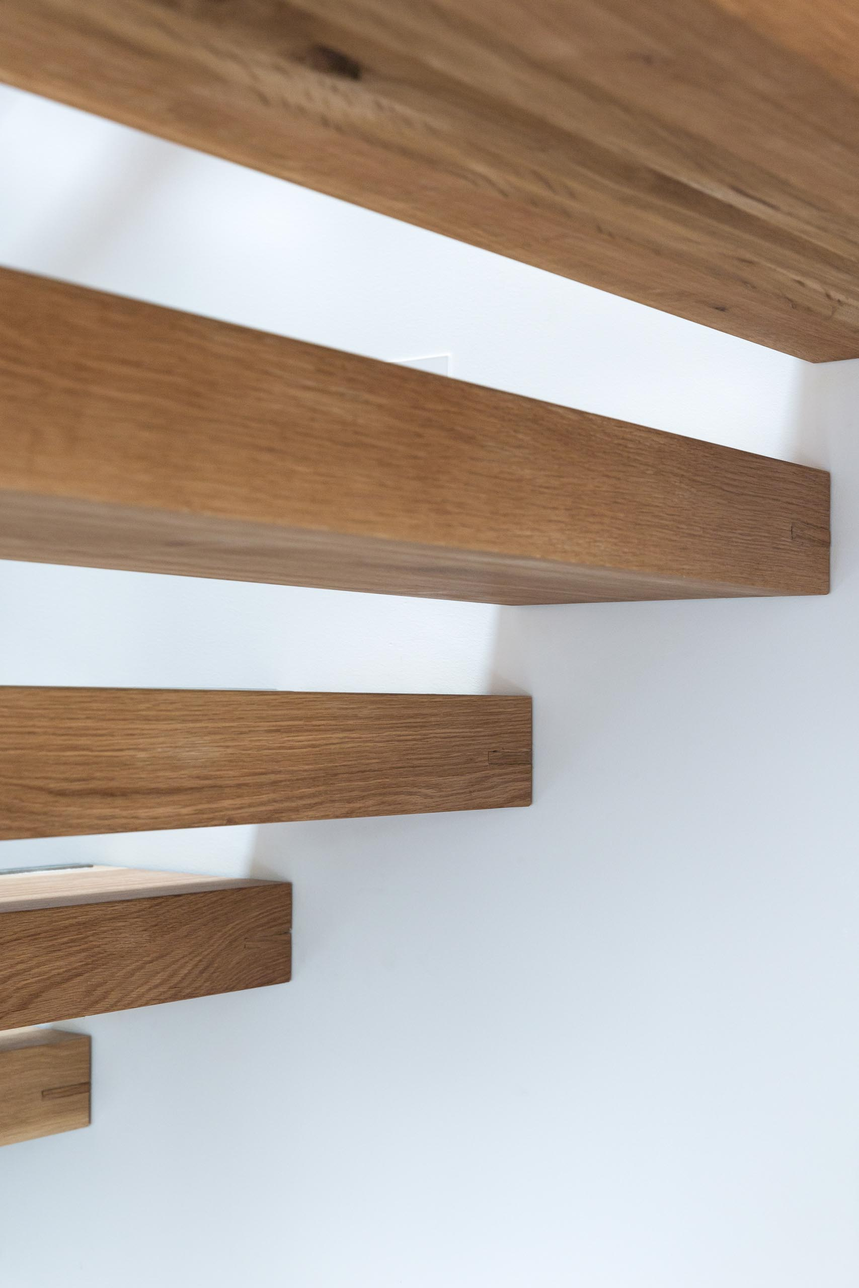 A steel and floating oak staircase with robust timber balusters and embedded stainless steel strips within the stair treads that create a non slip surface.