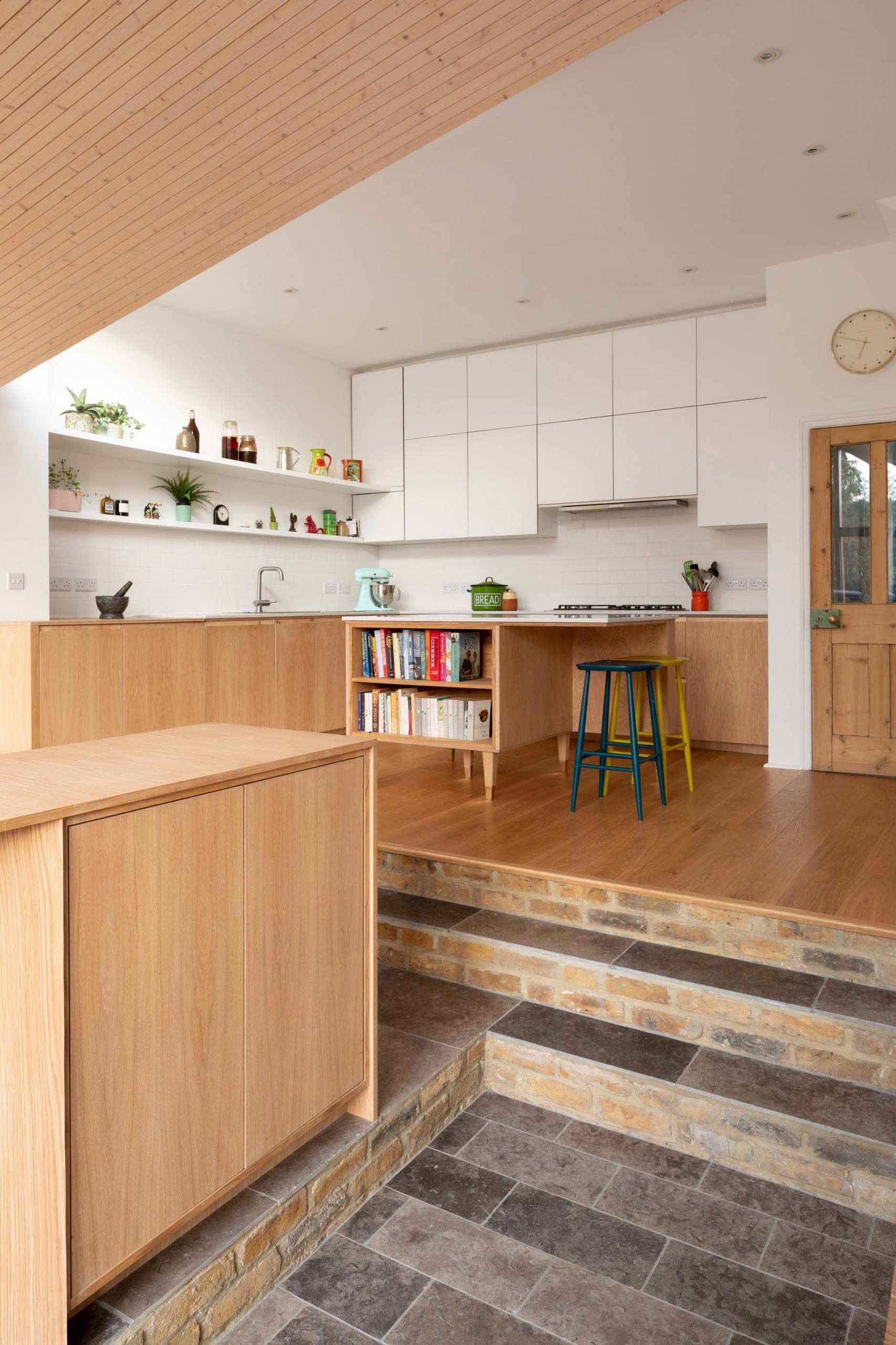 A contemporary kitchen with minimalist white cabinets that fill the wall, open white shelving, a small island with recipe book storage, and lower wood cabinets.