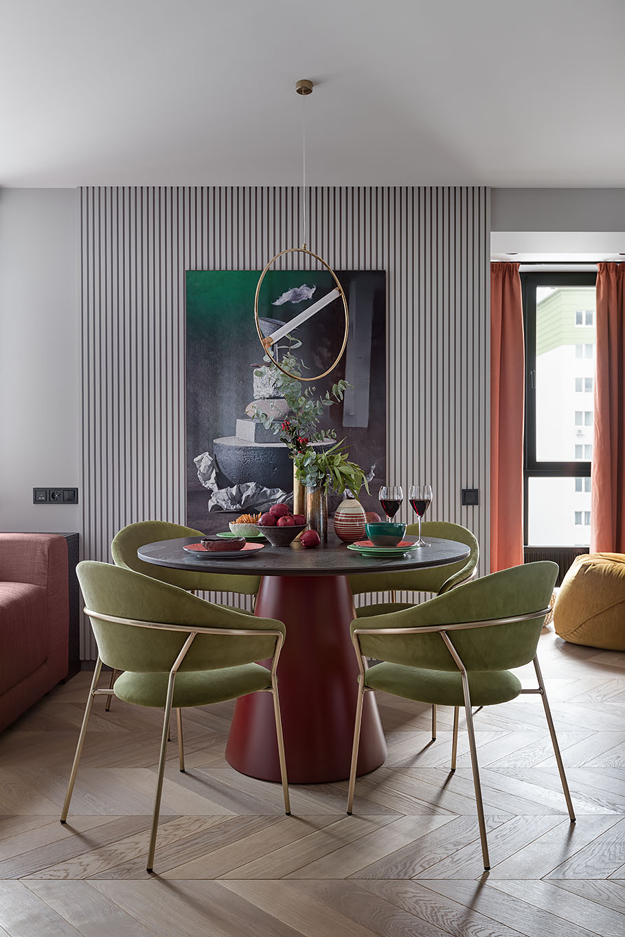 Separating the living space from the kitchen is a round dining table, a minimalist pendant light, and chairs with metallic frames.