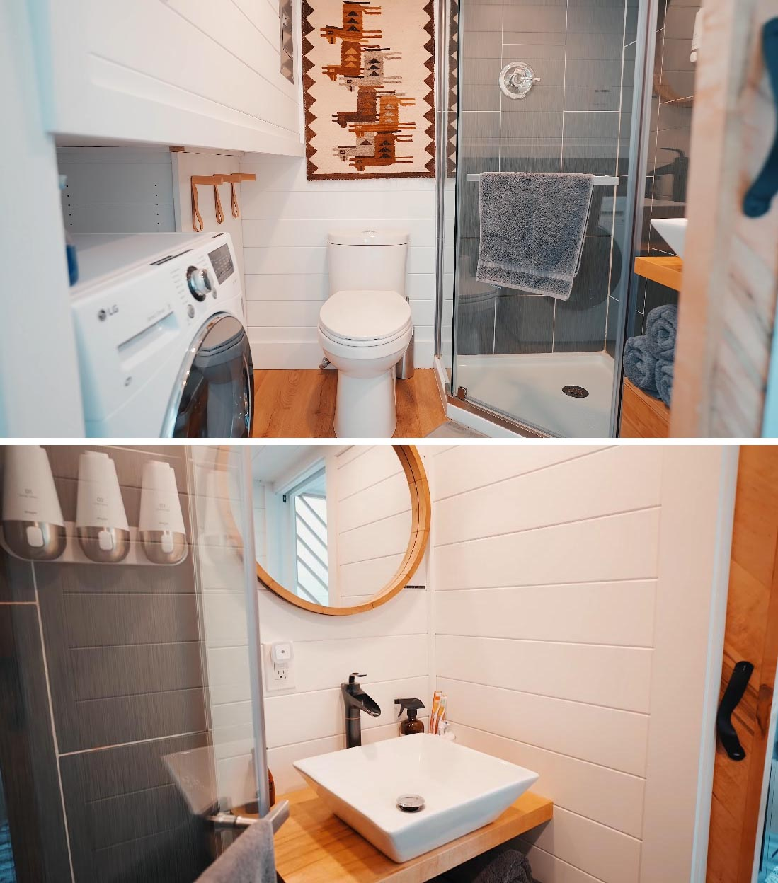 The bathroom of this Scandinavian-inspired tiny home includes a toilet, a shower with vertical gray tiles, a wood vanity with round mirror hanging on the wall above, and a washing machine.