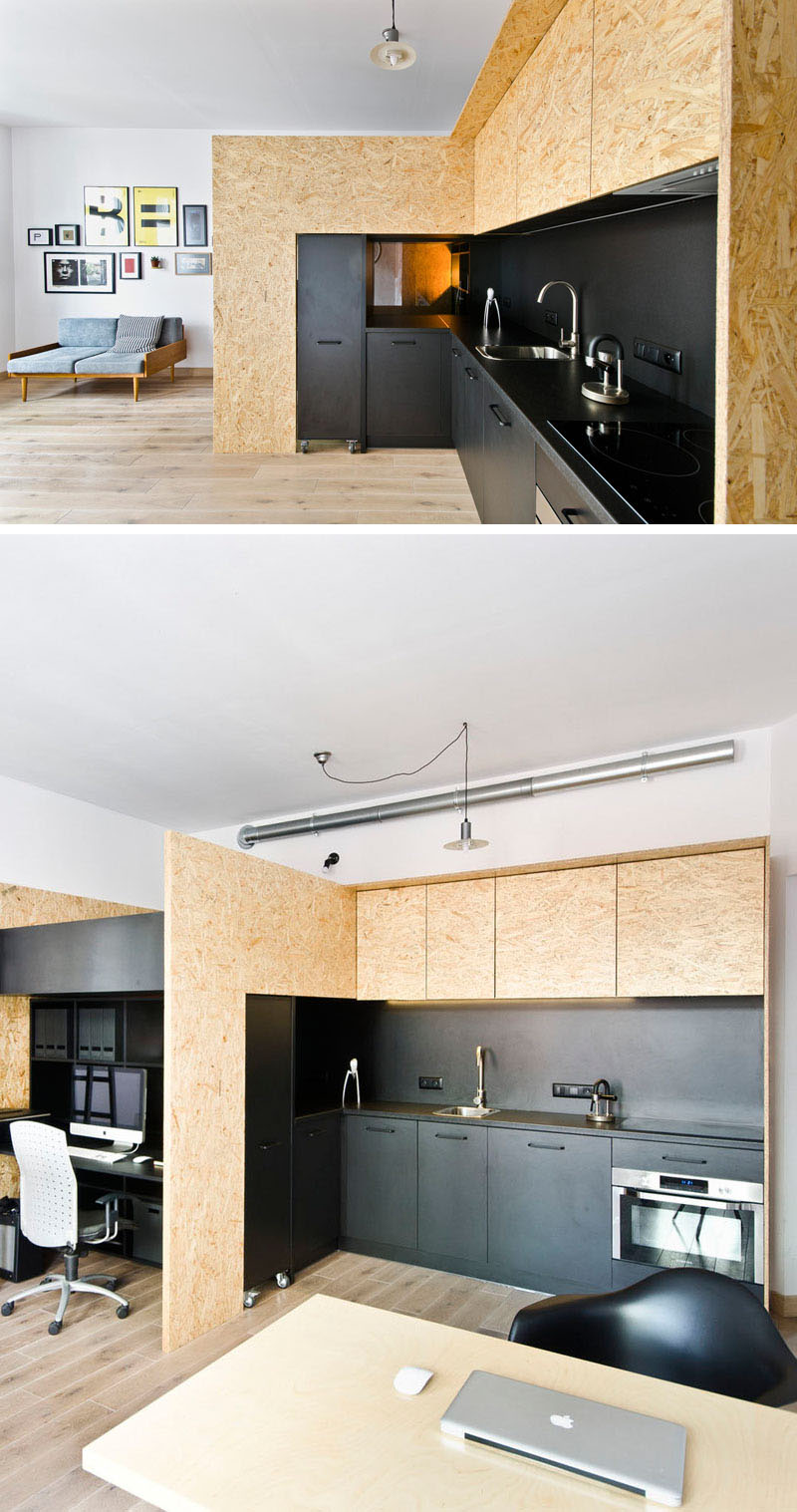 mode:lina architekci designed the interior of a small apartment that includes a black kitchen.