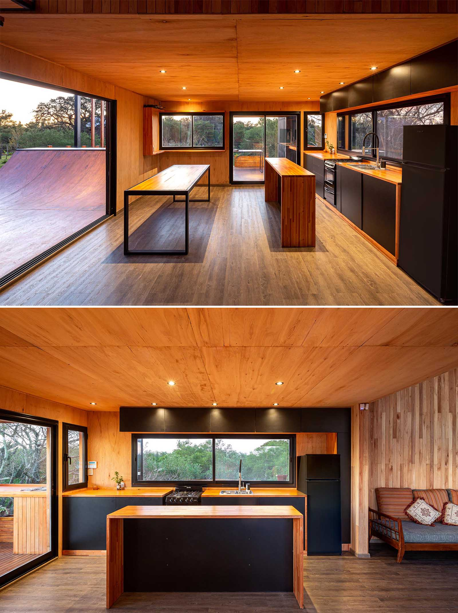 A modern house with a wood and black kitchen and dining area, and a skateboard ramp.