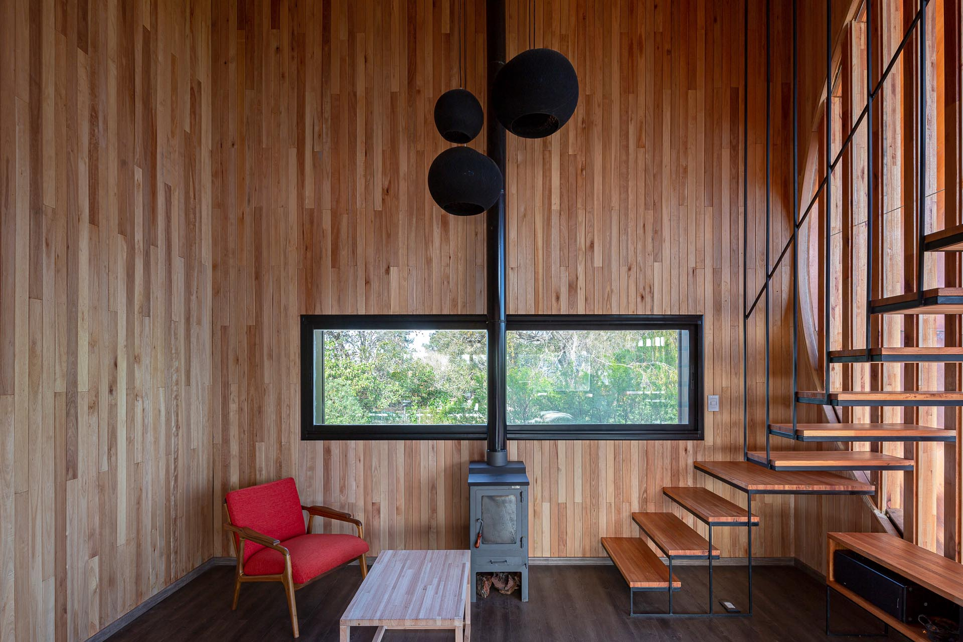 A small and modern house with a wood-lined interior, and a black fireplace that matches the window frames.
