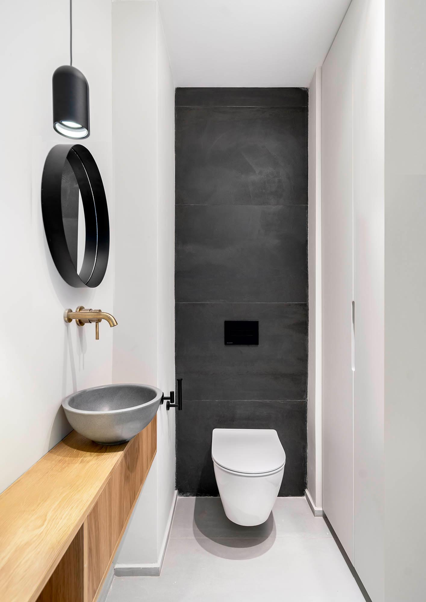 A powder room with large format matte black tiles line the wall behind the toilet, a wood vanity topped with a gray vessel sink, and bronze hardware.