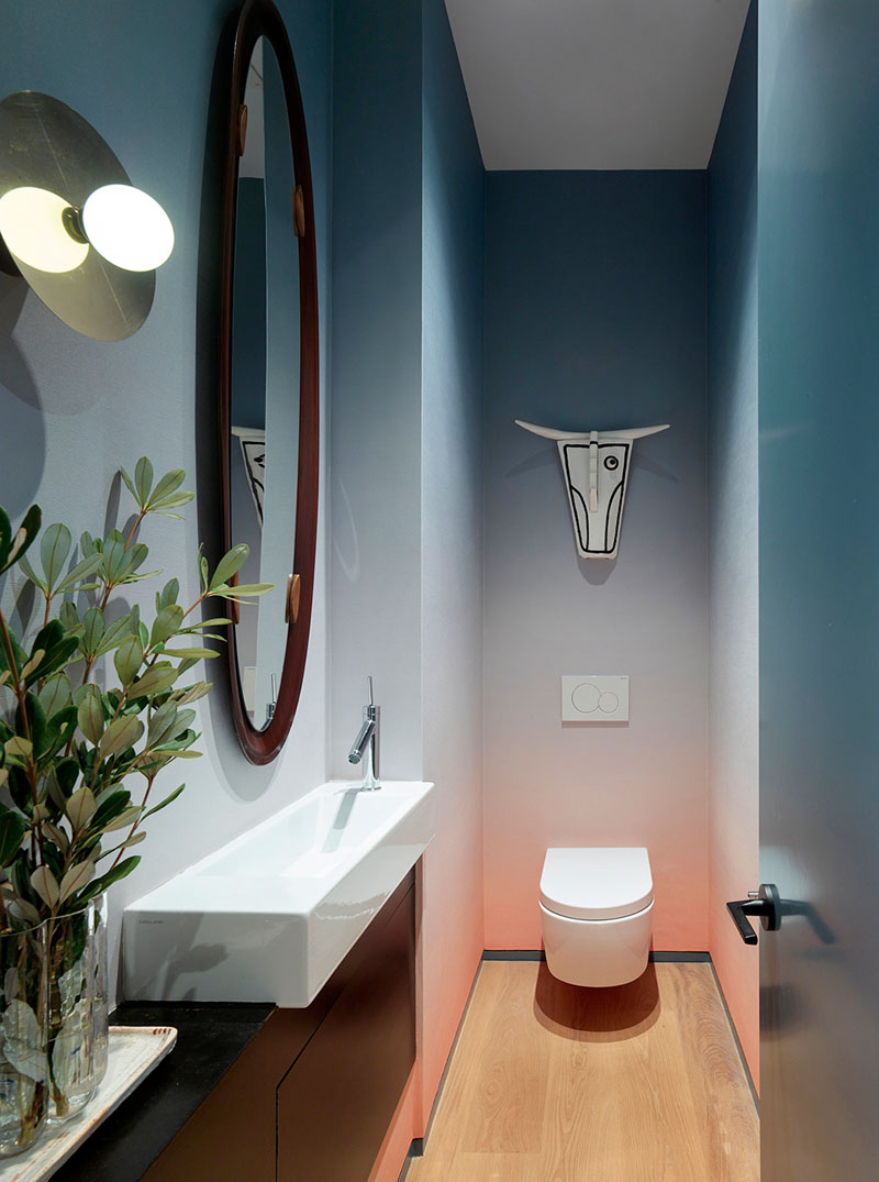 A colorful powder room that features an ombre wallpaper and an ox mask by Norwegian artist Arne Lindaas.