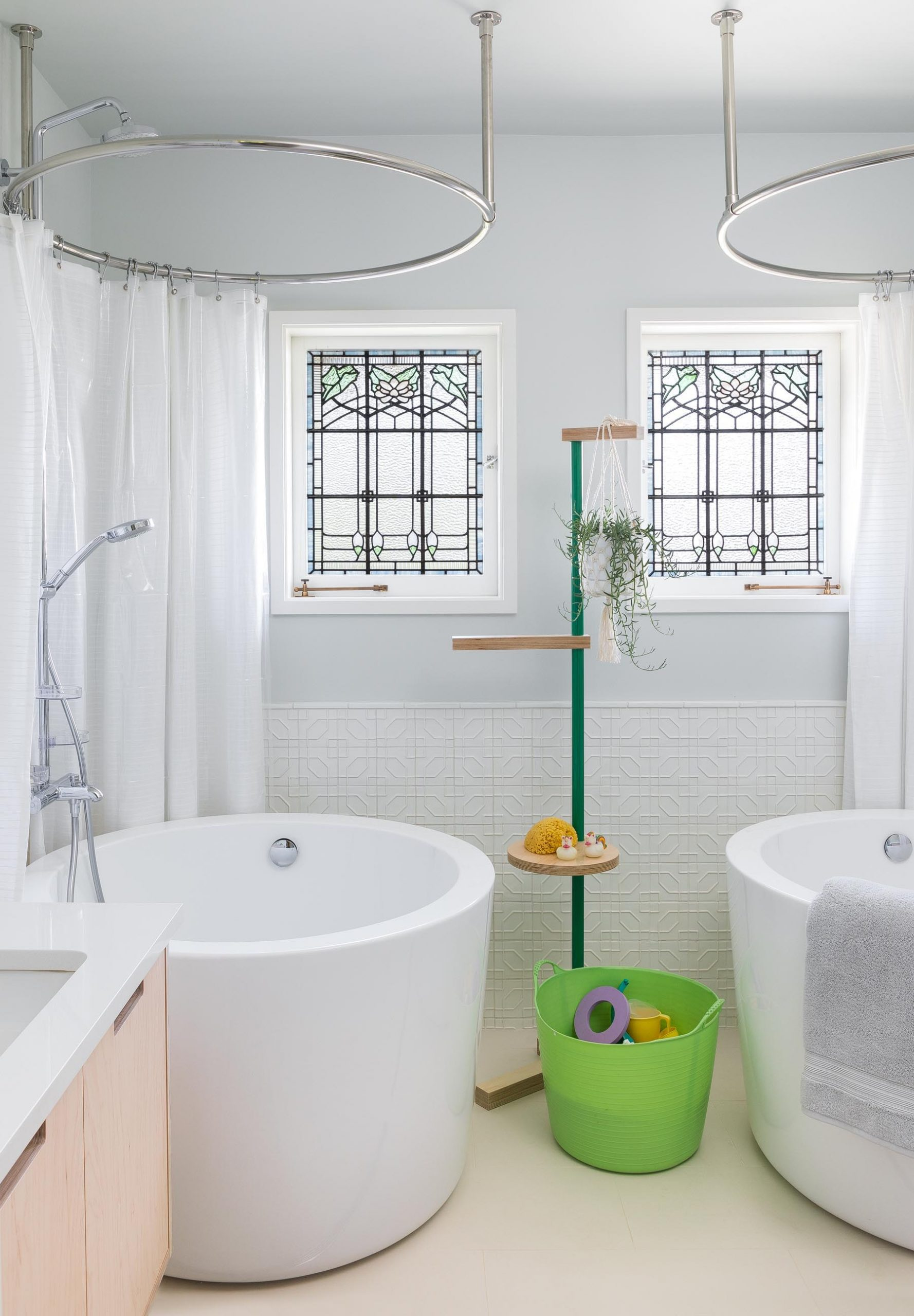 A remodeled bathroom with two deep soaking tubs, matching stained glass windows, tiles that cover the lower portion of the wall, and a plant stand that doubles as shelving.