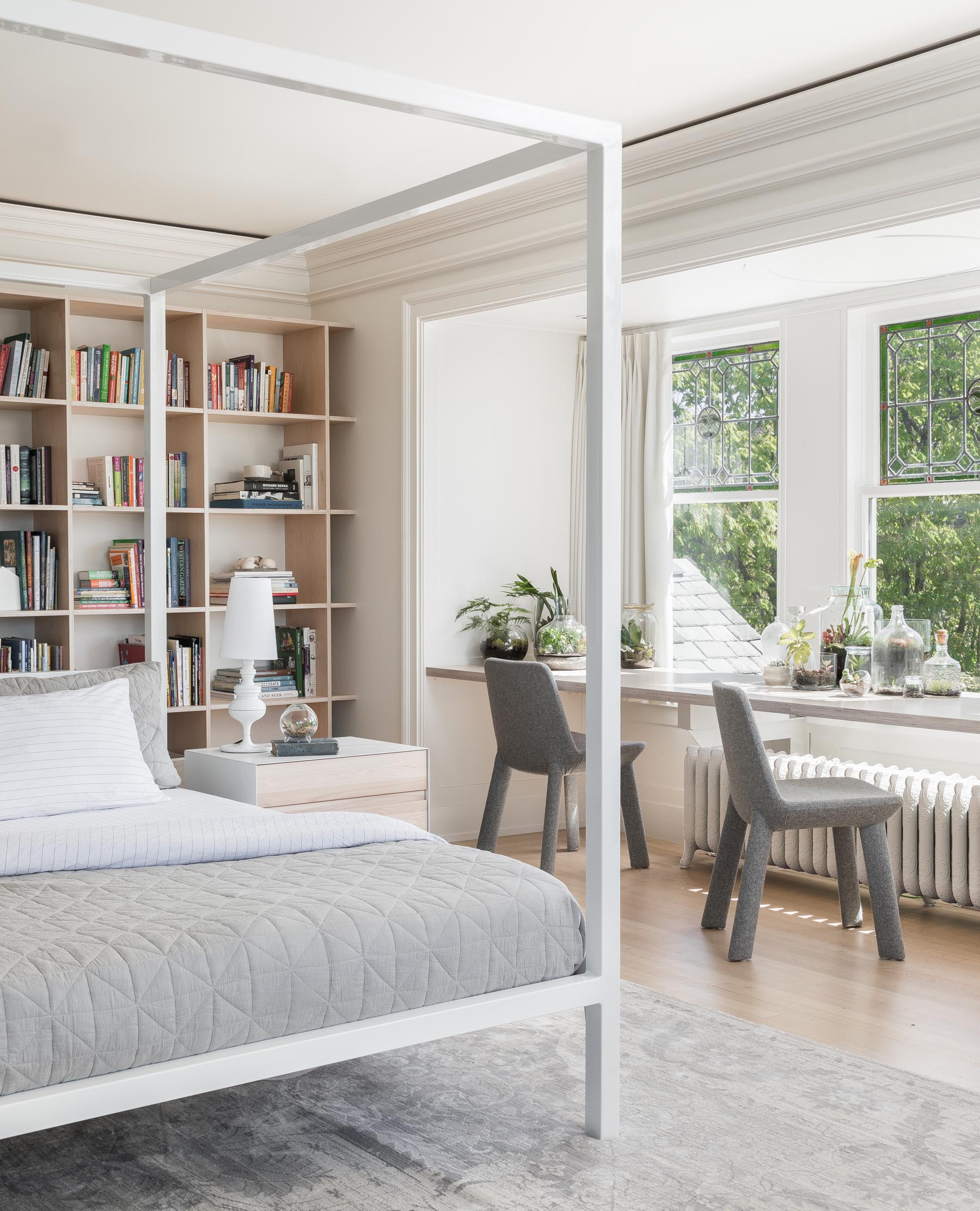 In a modern master bedroom, a wood desk spans the width of the windows, and provides a place for two to sit at.
