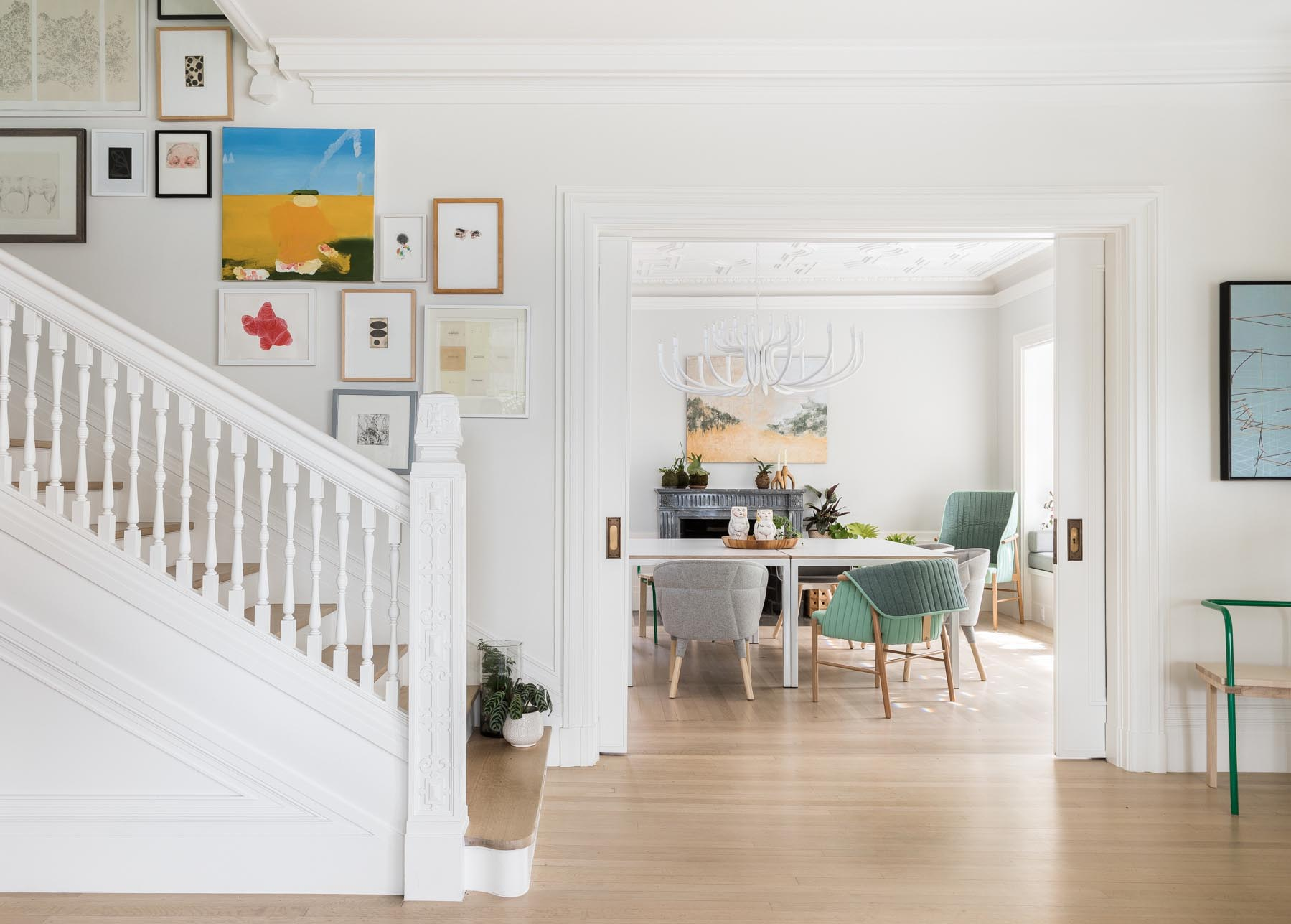 The remodeled contemporary interior includes wood floors and furnishings, and yet still retains some of the original design elements, which have been painted white, like the pocket doors, carved wood columns, and banister.